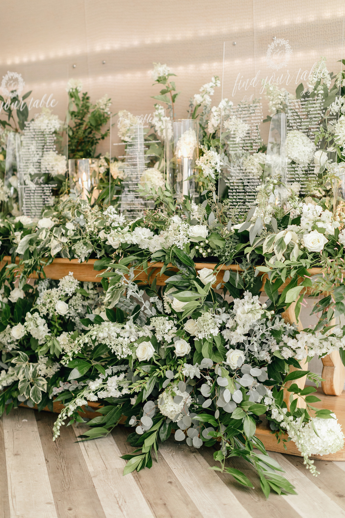transparent seating chart surrounded by white flowers and greenery