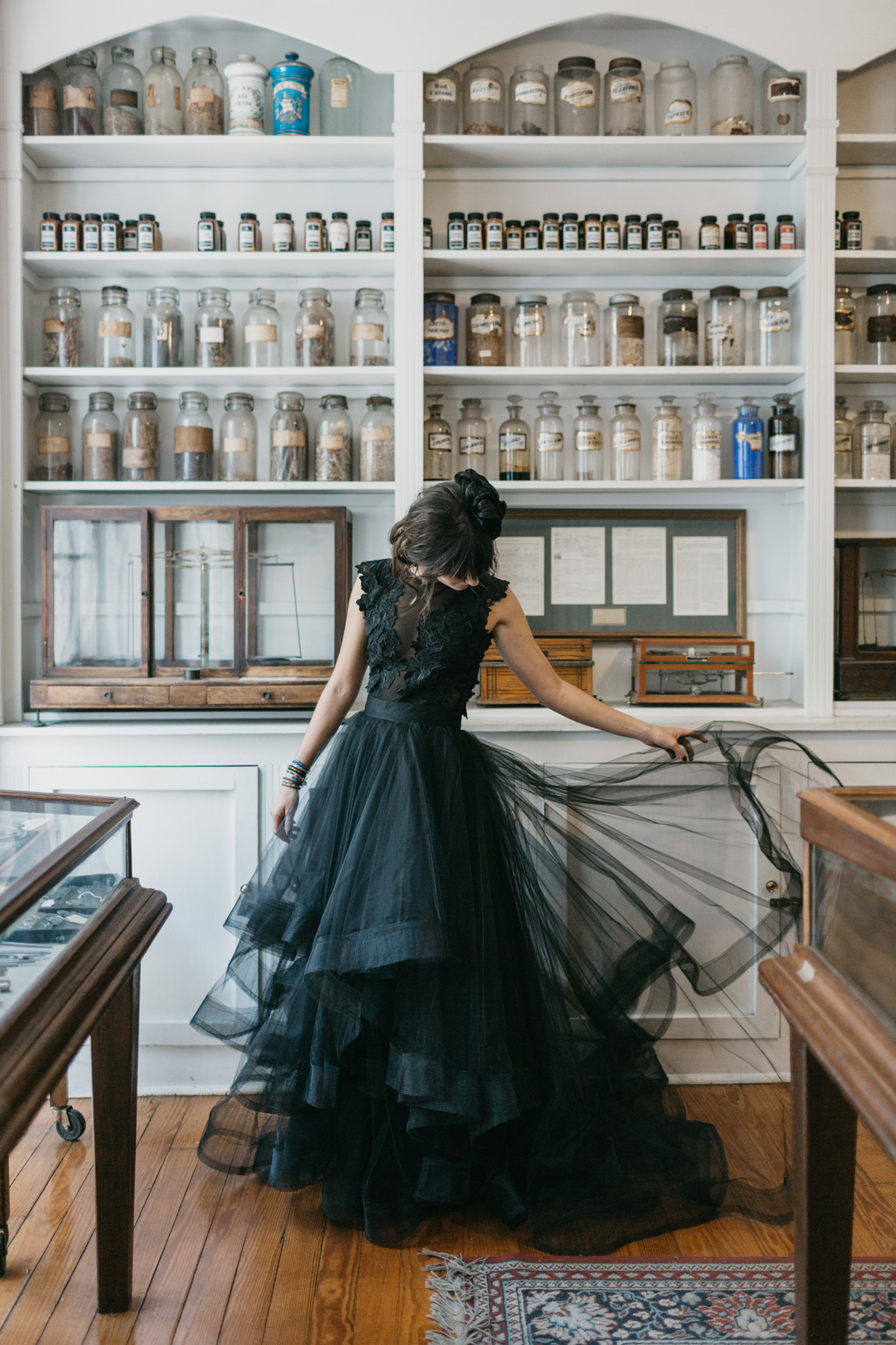 bride wearing black posing in front of apothecary cabinet