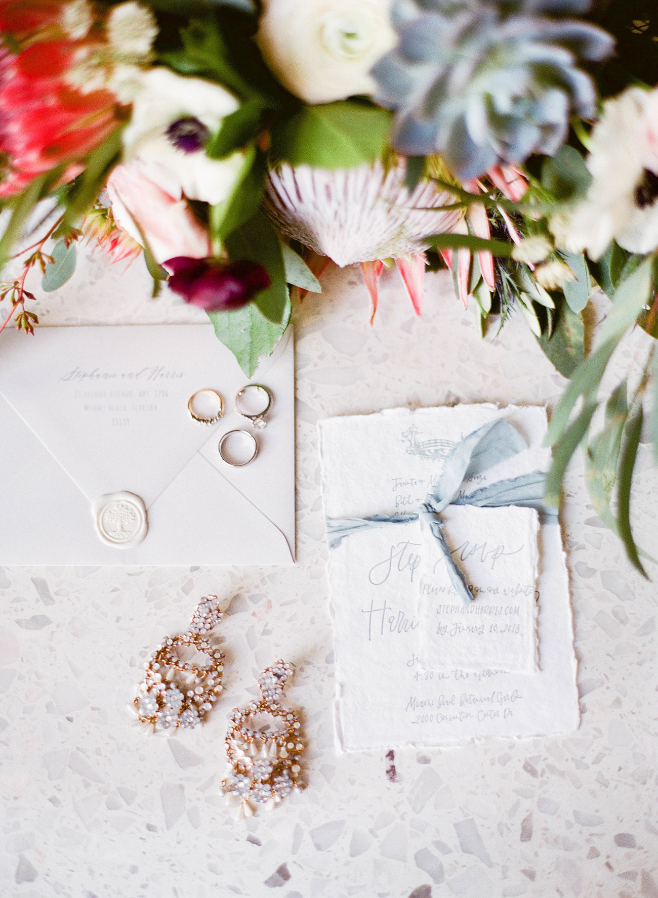 organic handmade and hand torn paper wedding invites with blue ribbon