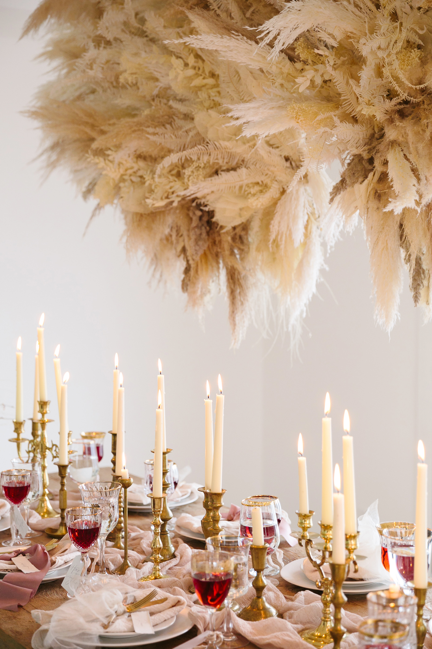 romeo and juliet valentines day party table setting with gold candle sticks and glasses of wine