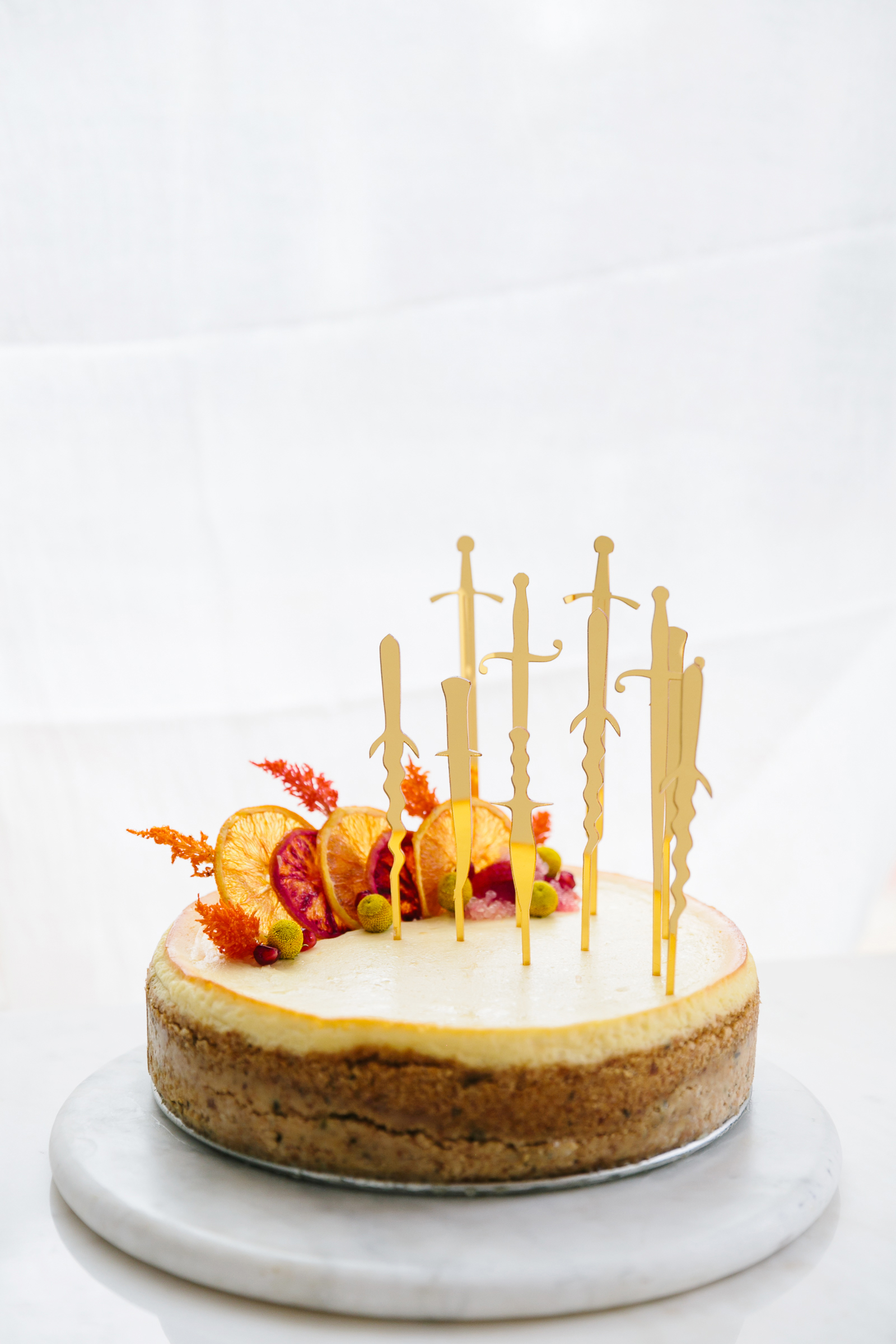 romeo and juliet valentines day party cheesecake decorated with gold knives and orange slices