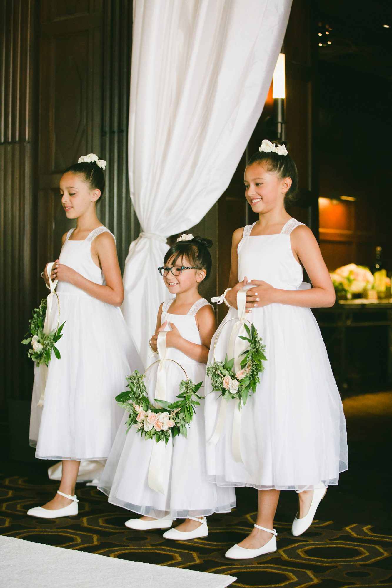 flower girls holding hoops with floral arrangements