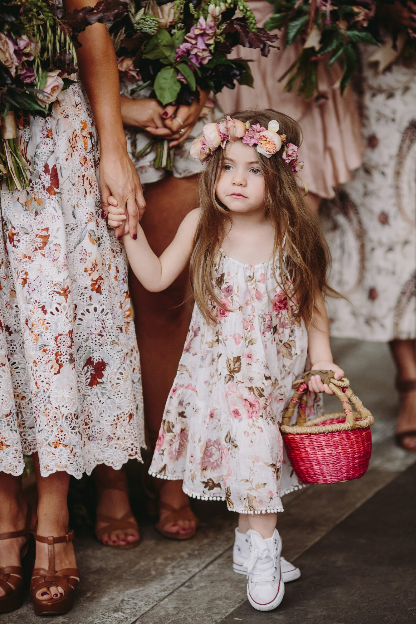 flower girl holding a red and brown basket