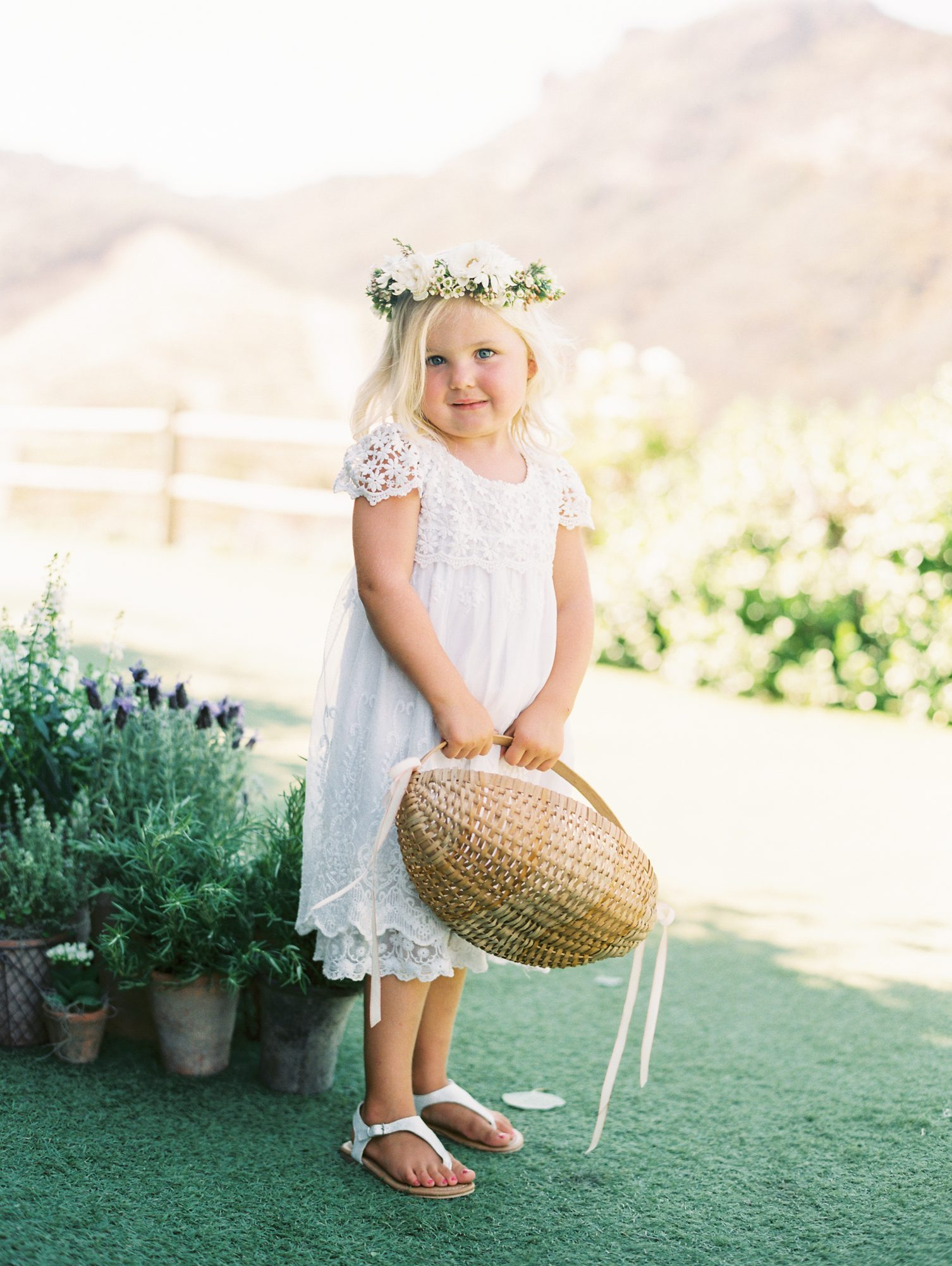 flower girl holding almond shaped wicker basket
