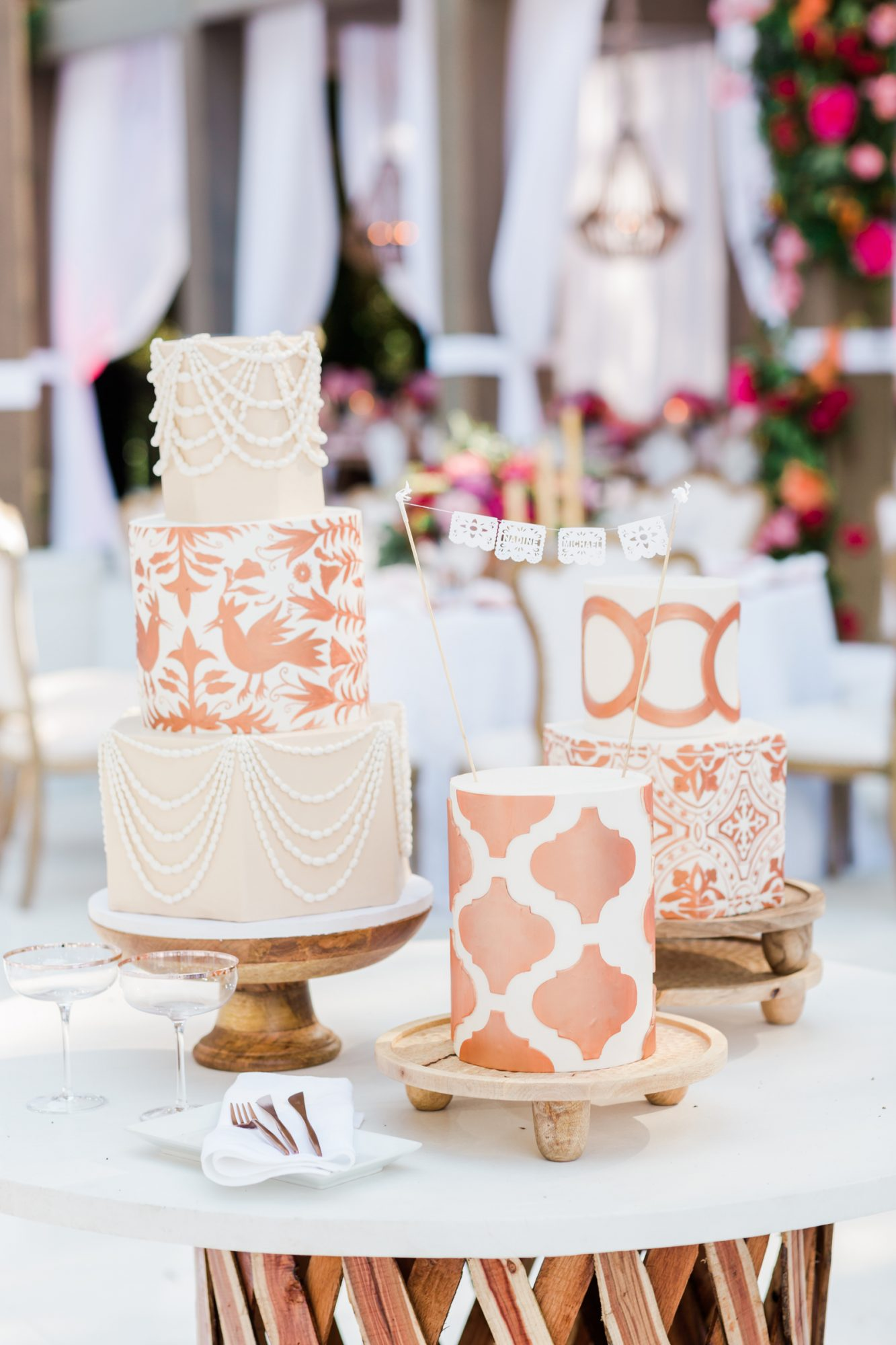 three wedding cakes with copper colored frosted designs