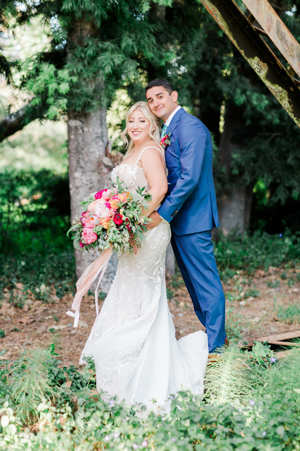 bride and groom pose in the forest