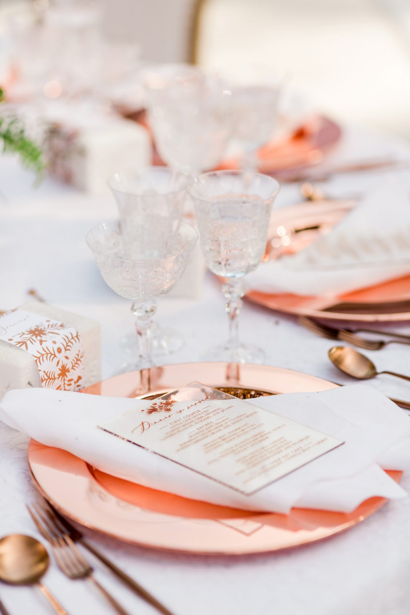 copper colored place settings with white linens