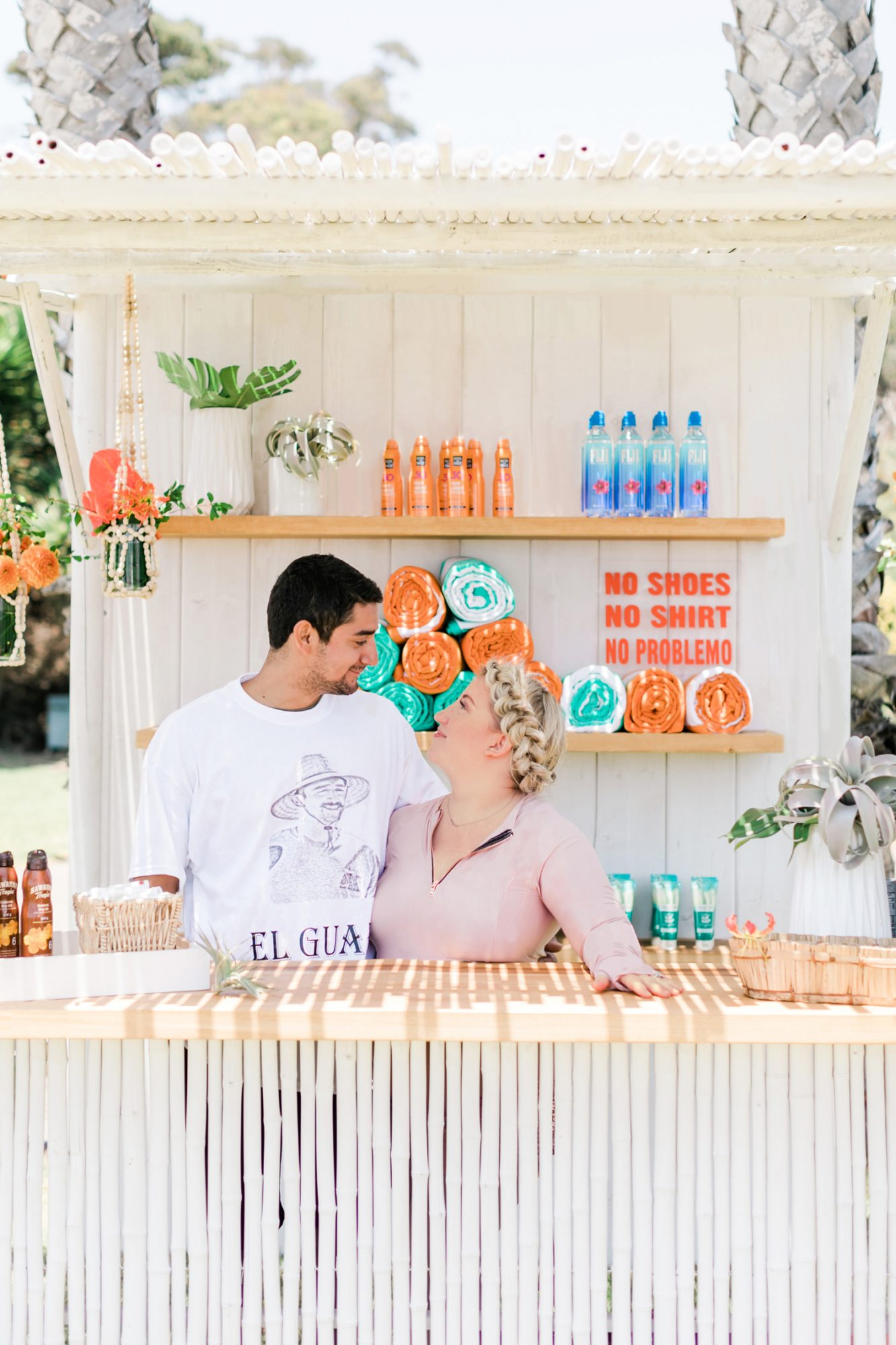 couple poses behind guest welcome bar