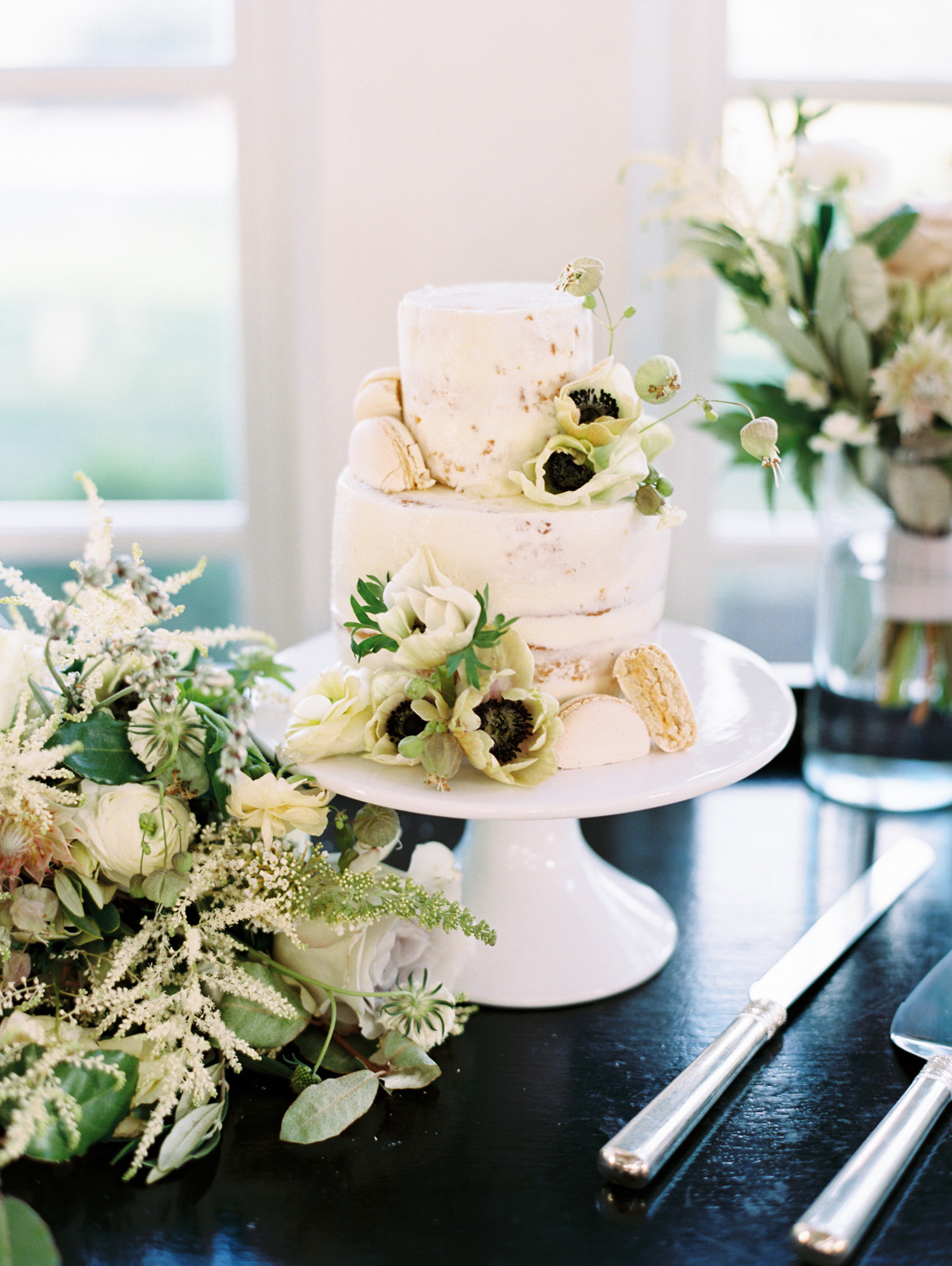 white frosted two tiered wedding cake with floral accents