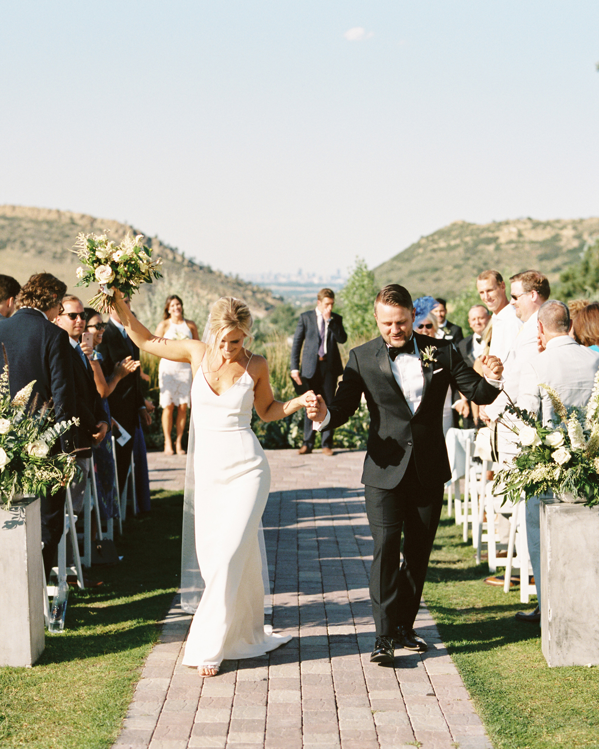 bride and groom dance down aisle during recessional