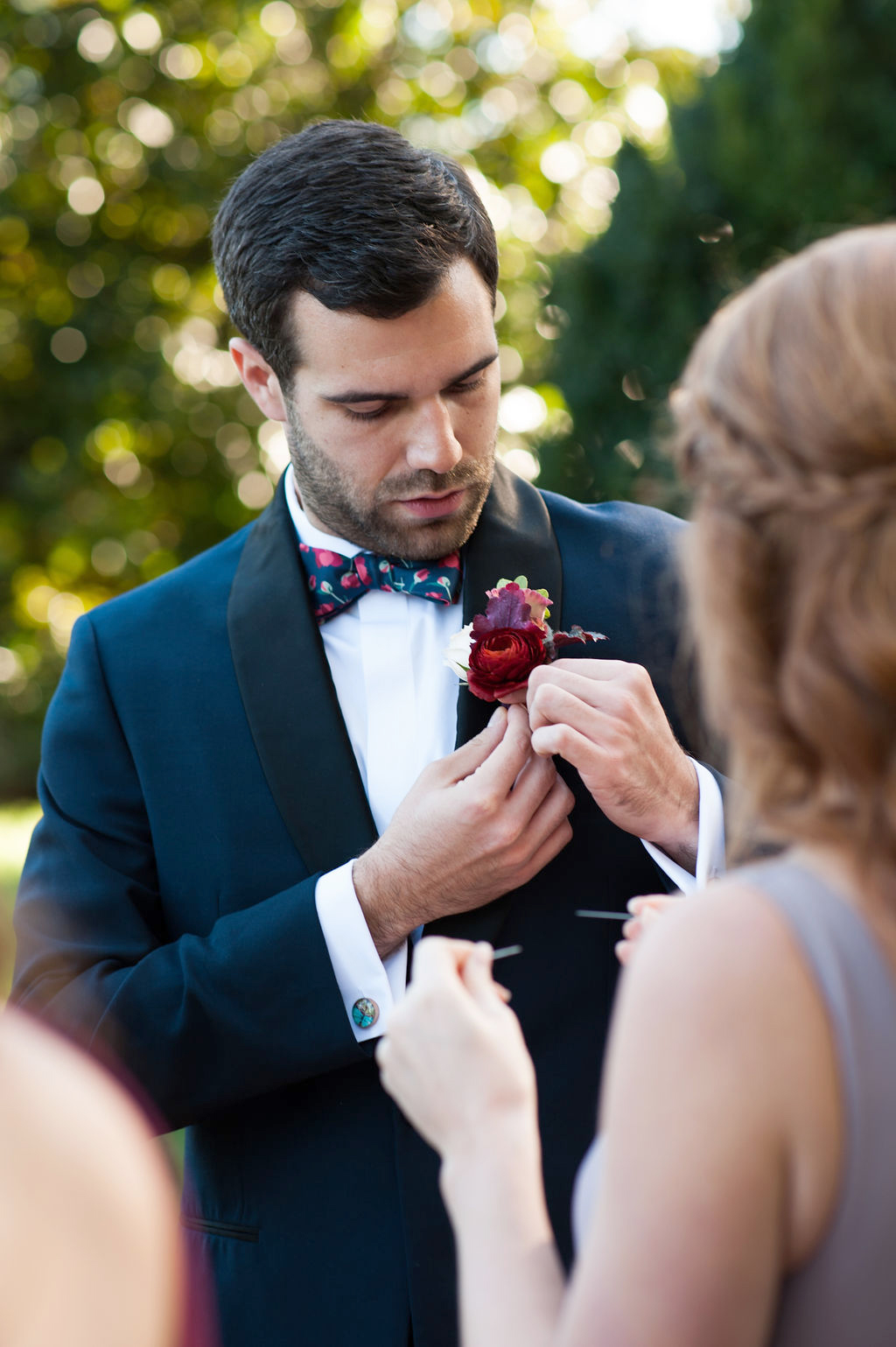 groom wearing navy tux pins red floral boutonniere