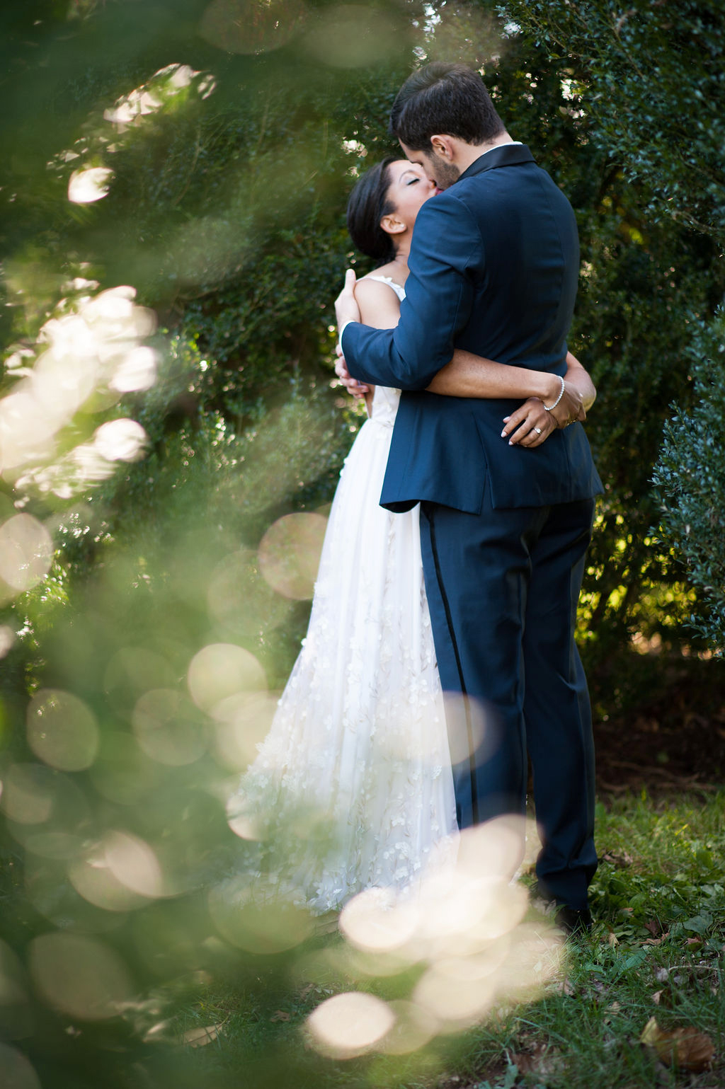 bride and groom hugging each other surrounded by greenery