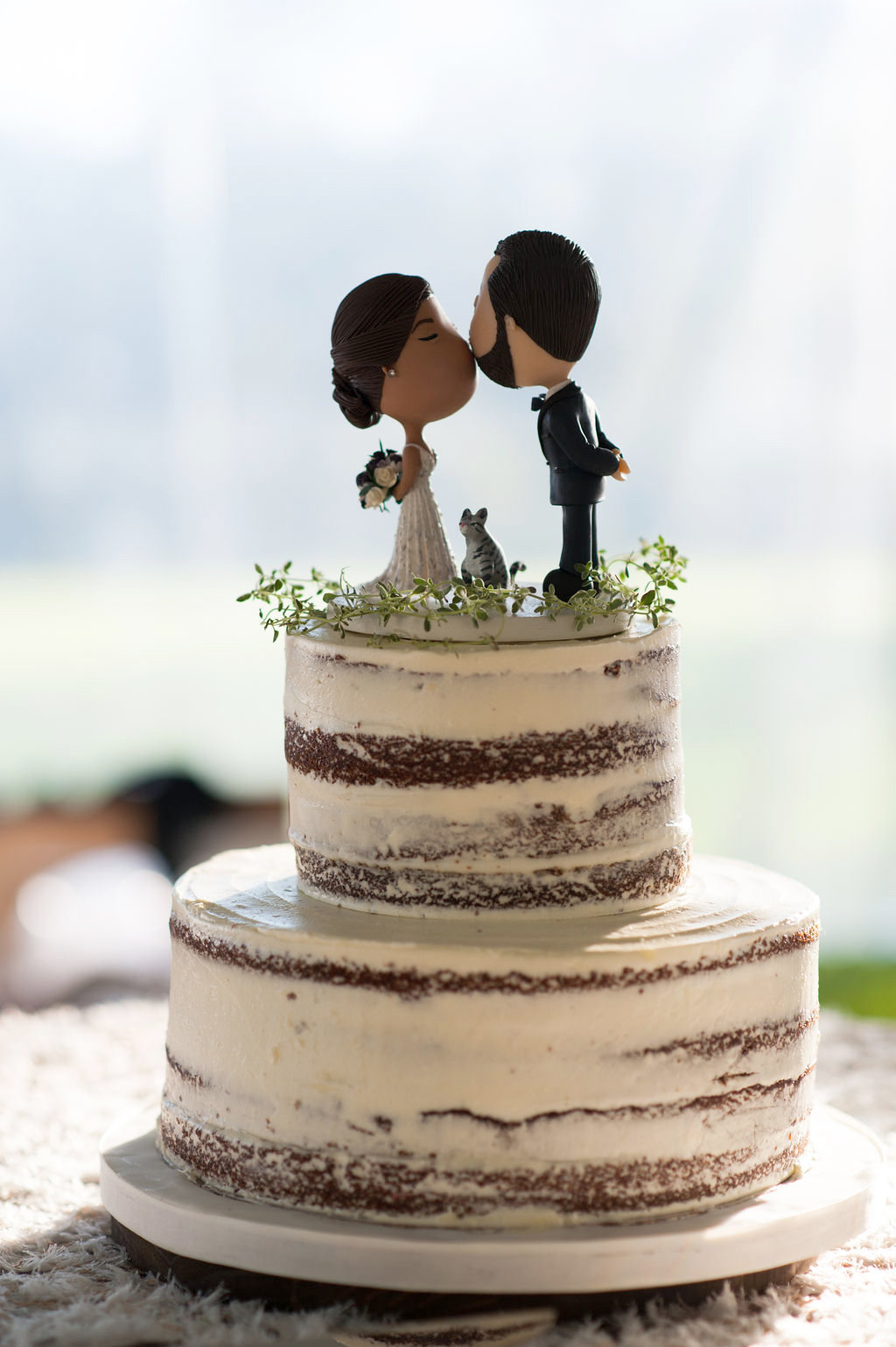 custom cake topper on double tier cake with thin white frosting layer