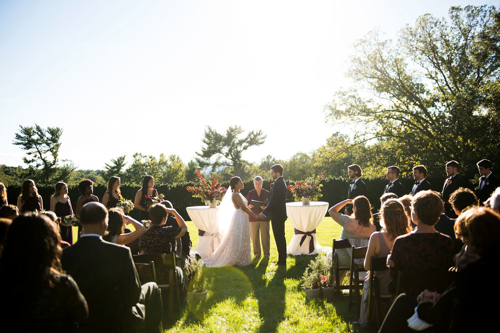 bride and groom during wedding ceremony as guests watch