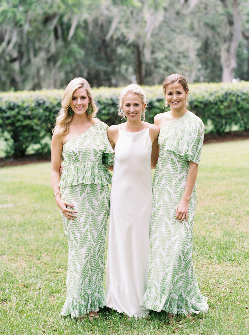 bride with bridesmaids wearing long white dresses with green leaf print