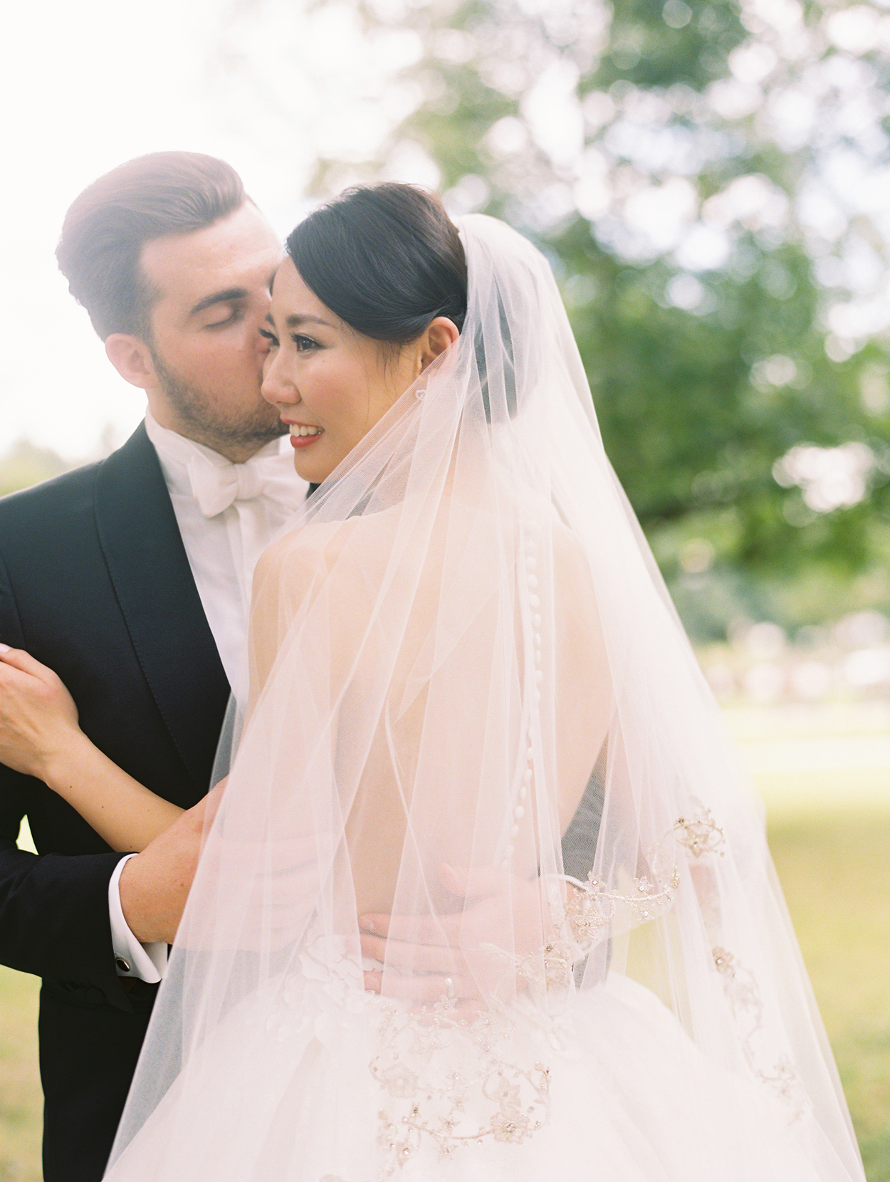 groom kisses bride's cheek while couple embraces