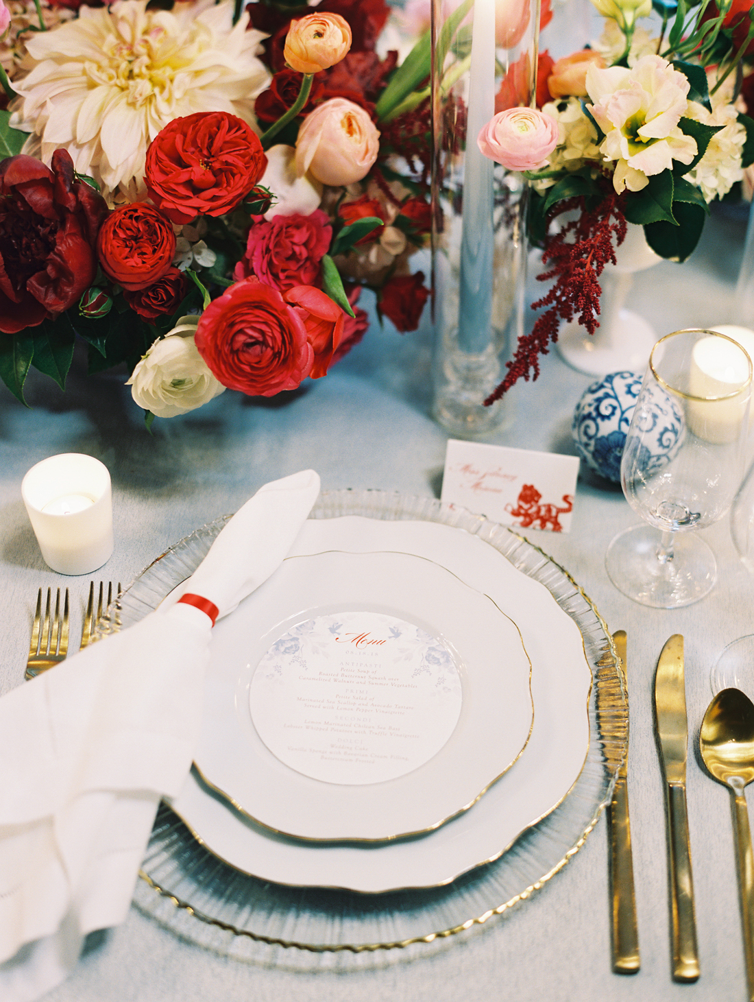 gold trimmed white plates with gold silverware and floral centerpieces