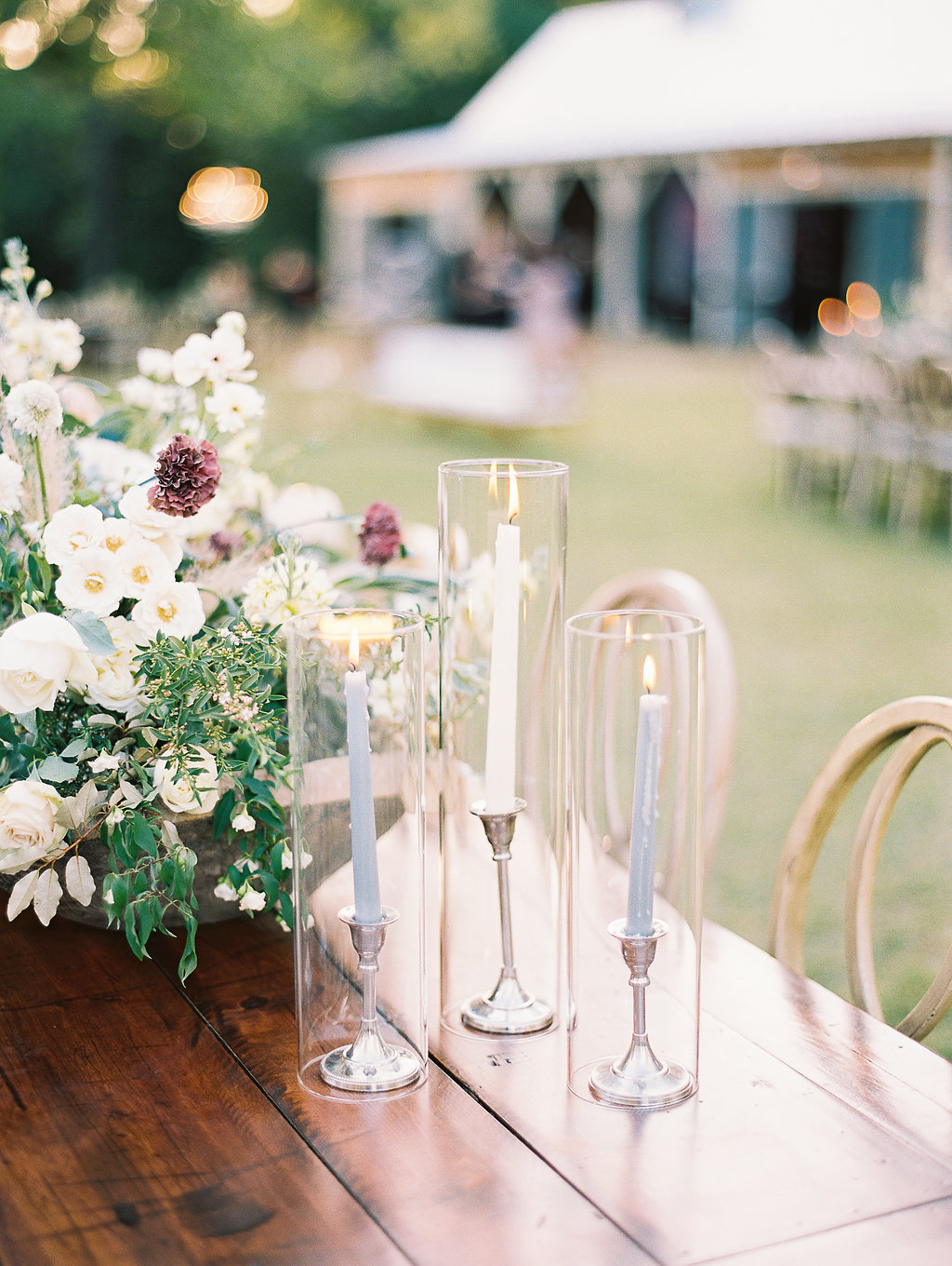 wood reception table adorned with candles in glass and neutral flowers