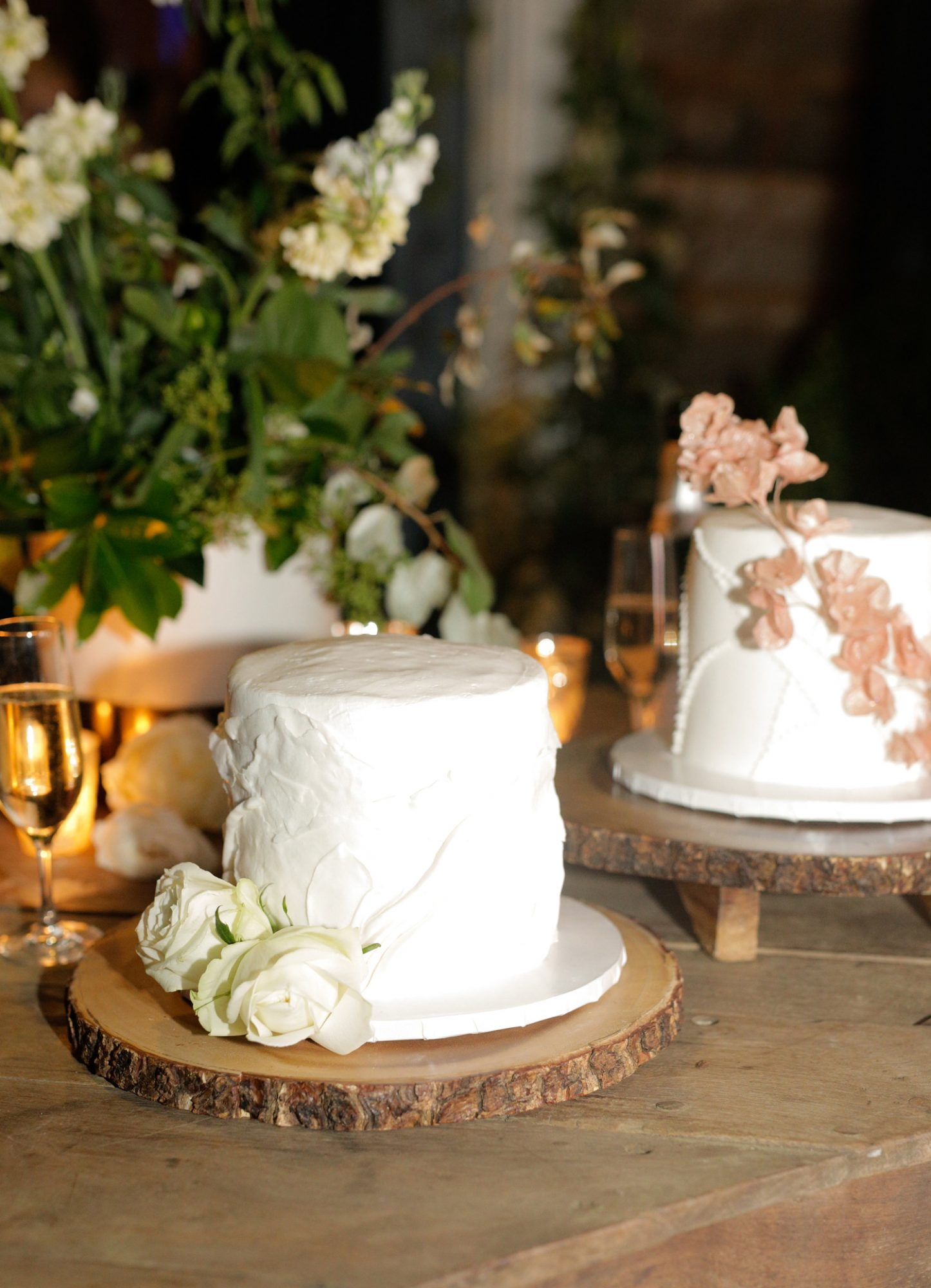 two white wedding cakes decorated with flowers