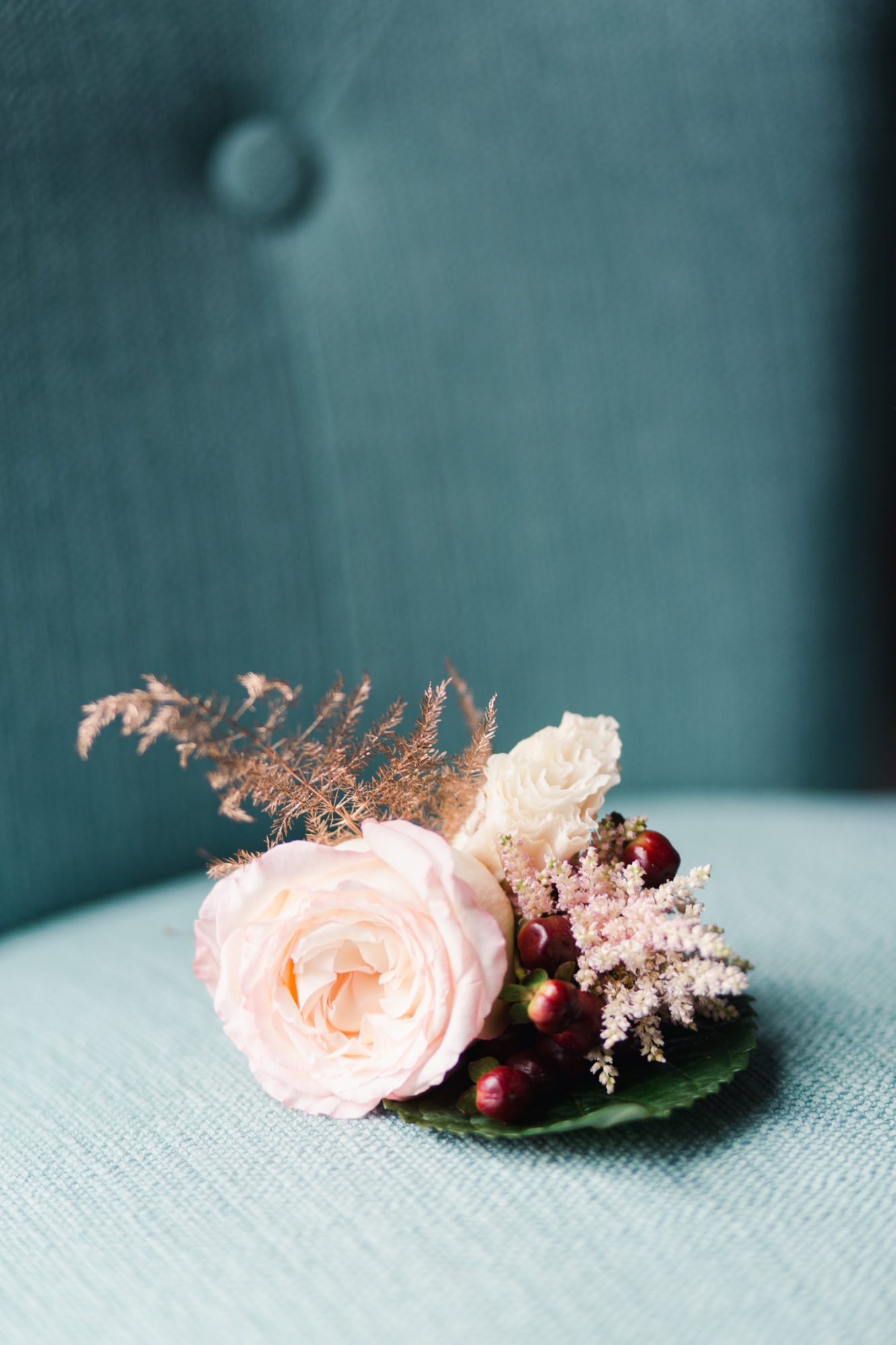 pink rose with green leaf boutonniere