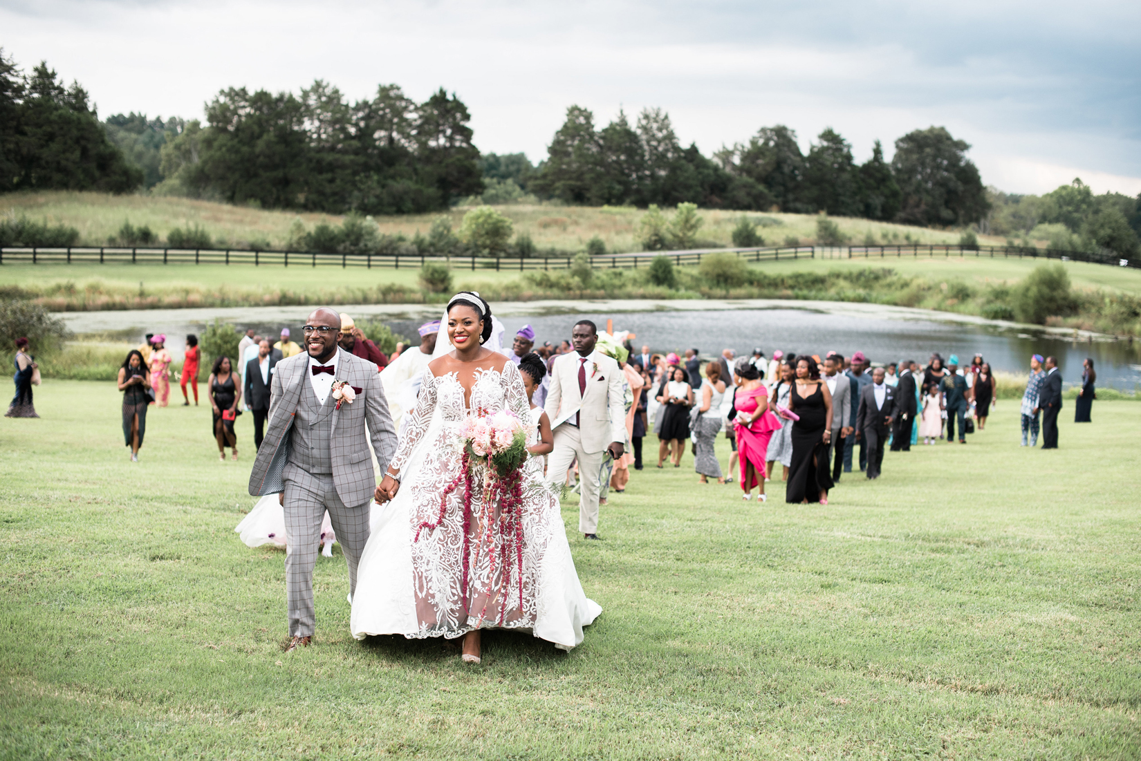 bride and groom walk away from ceremony with guests behind them