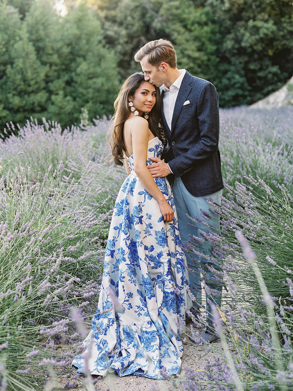 bride wearing white and blue gown with groom wearing blue suit in field