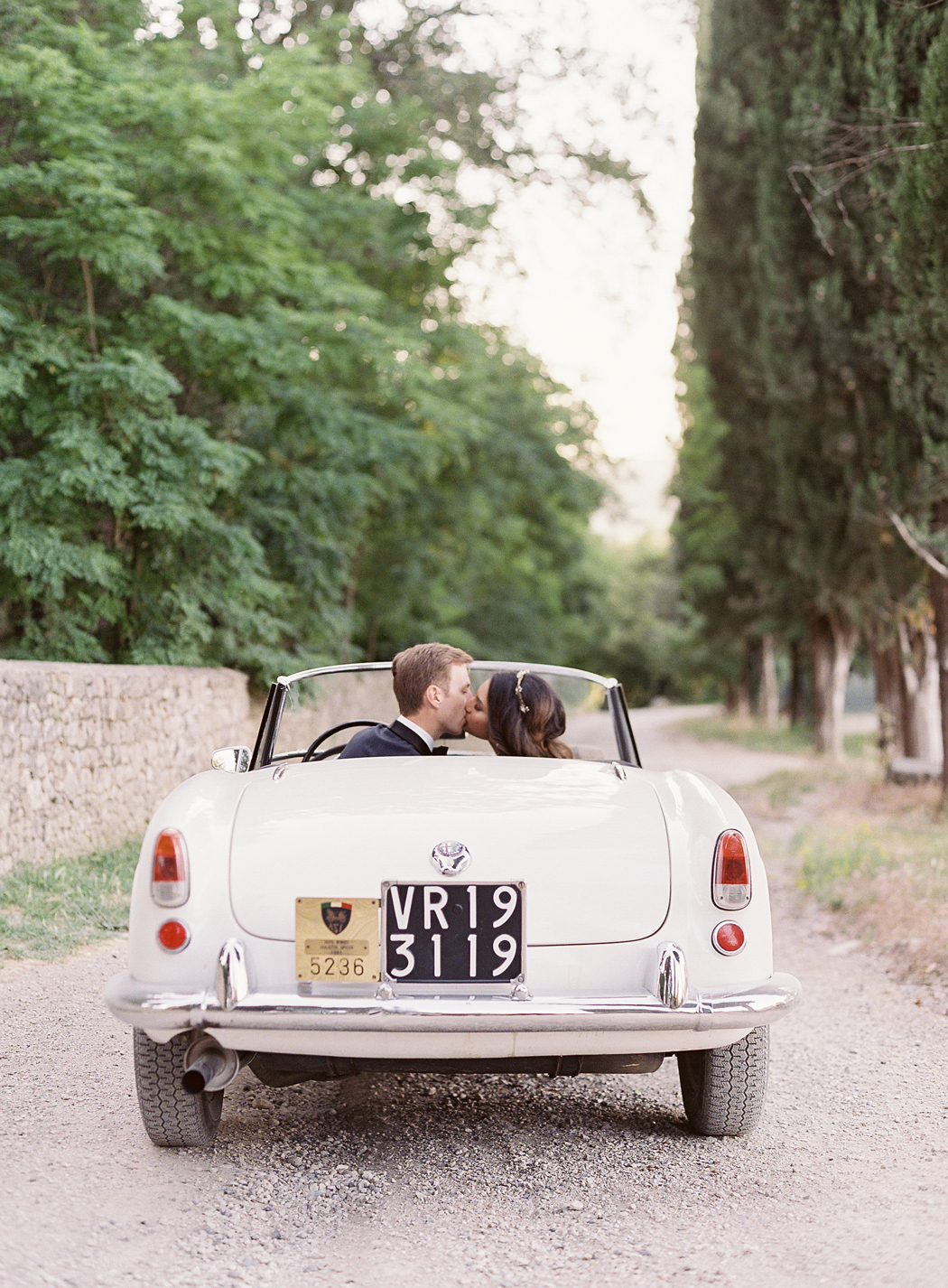 bride and groom sit in white vintage car
