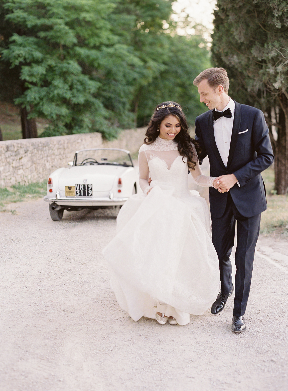 bride and groom hold hands smiling next to vintage white car