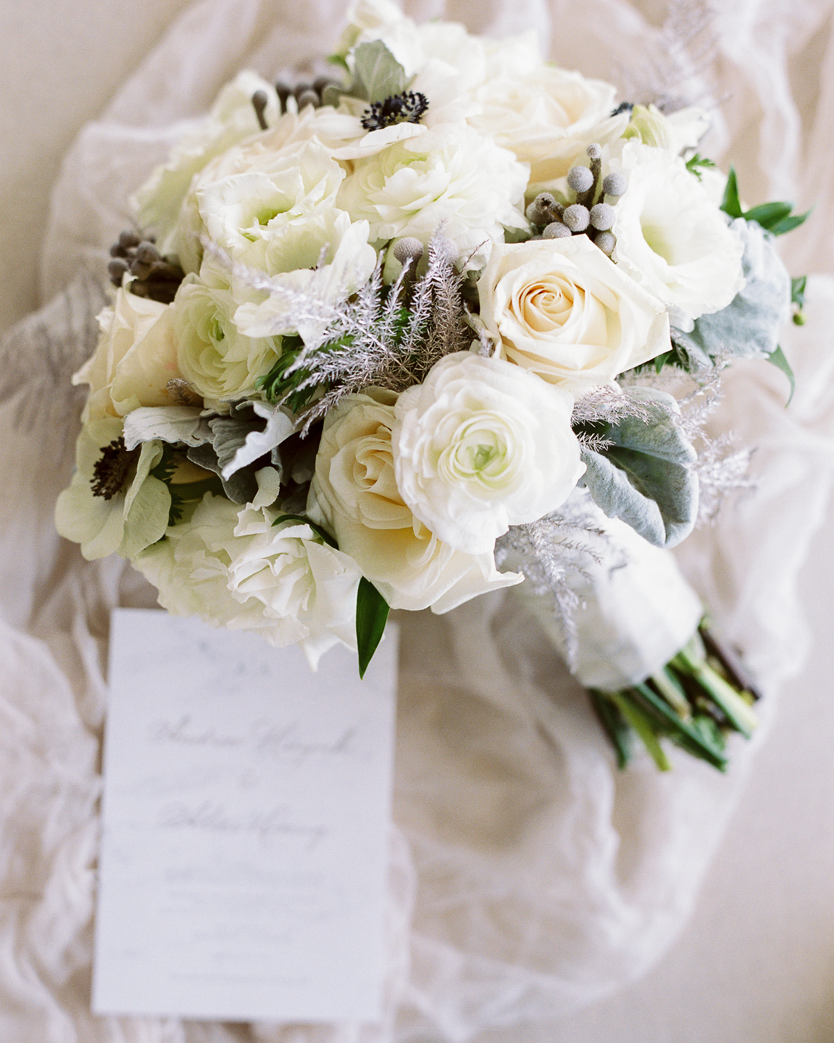 white rose wedding bouquet next to piece of paper