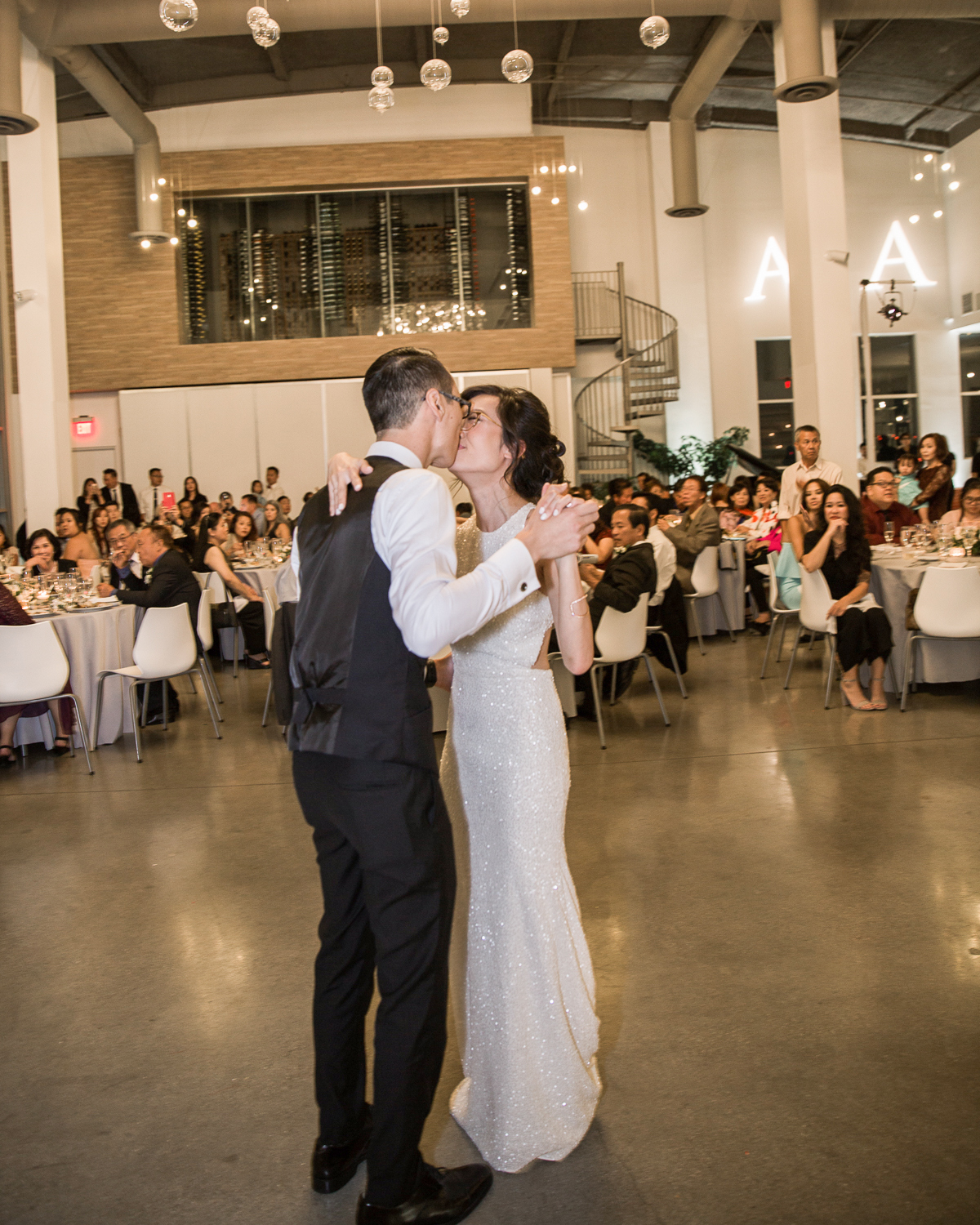 wedding couple first dance indoors around guests