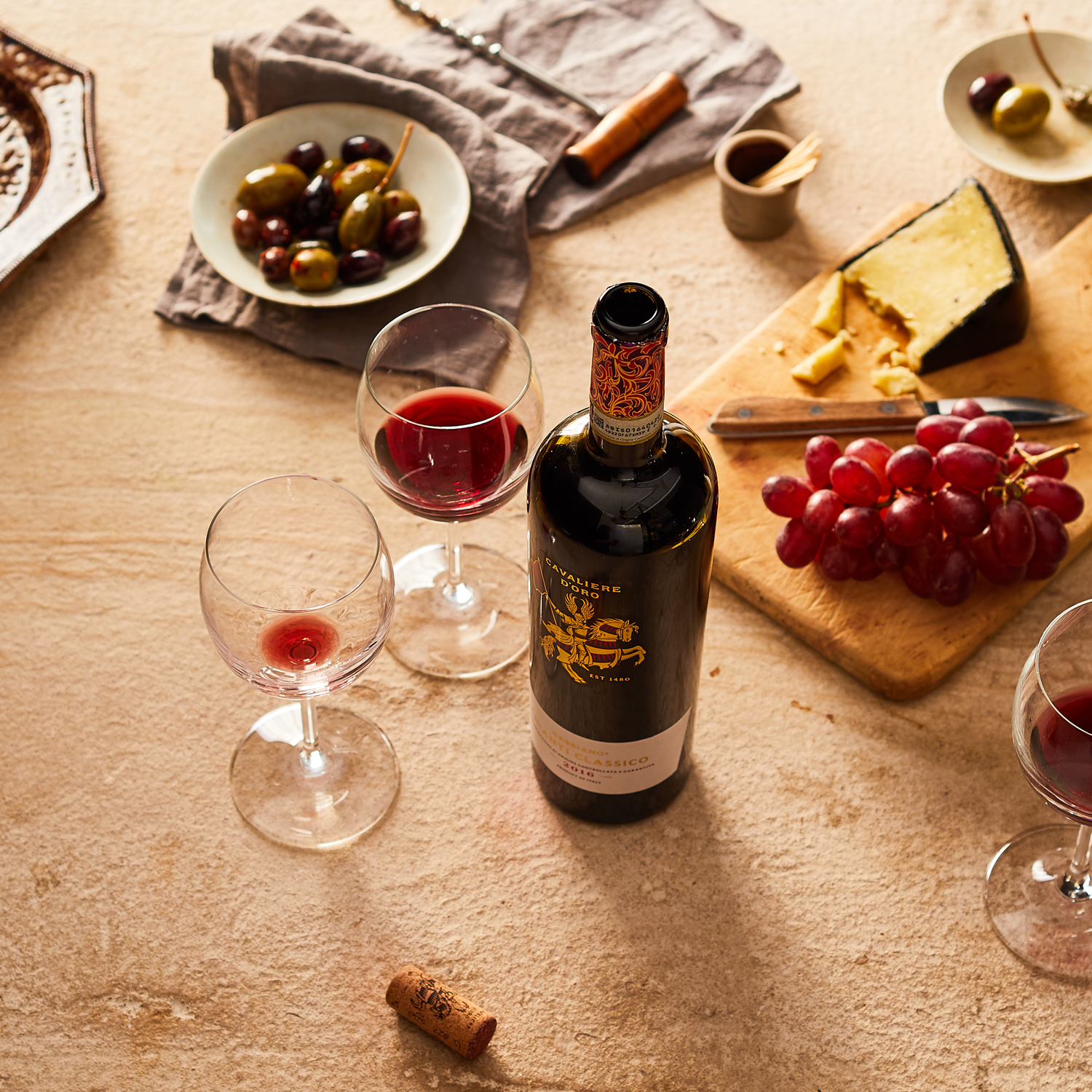 bottle of wine olives in bowl and cutting board with grapes and cheese