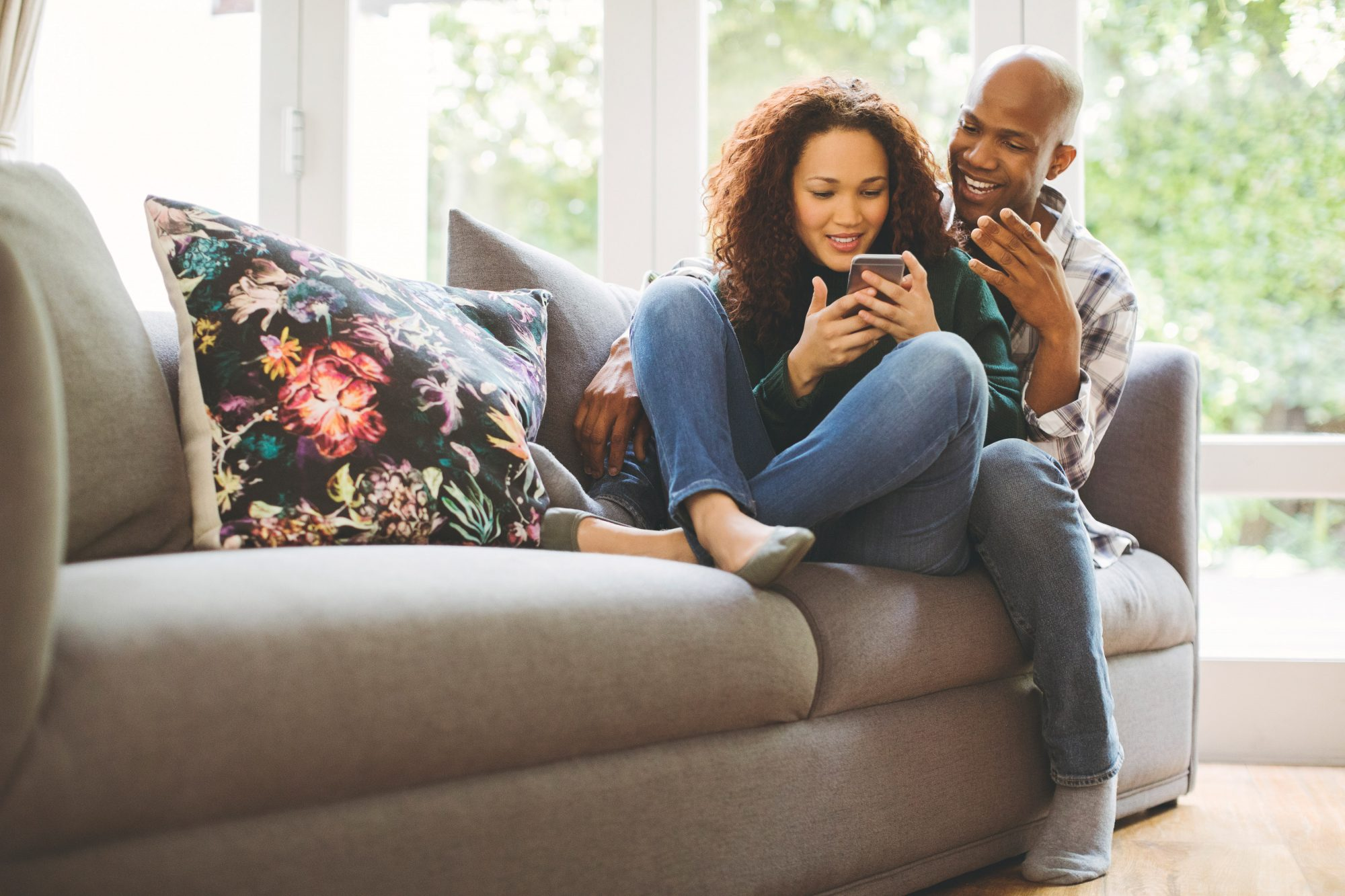 Couple Sitting on Couch Looking at Cell Phones