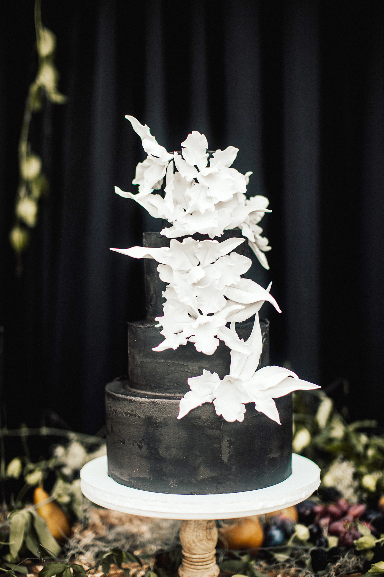 four tiered black frosted wedding cake with white floral accents