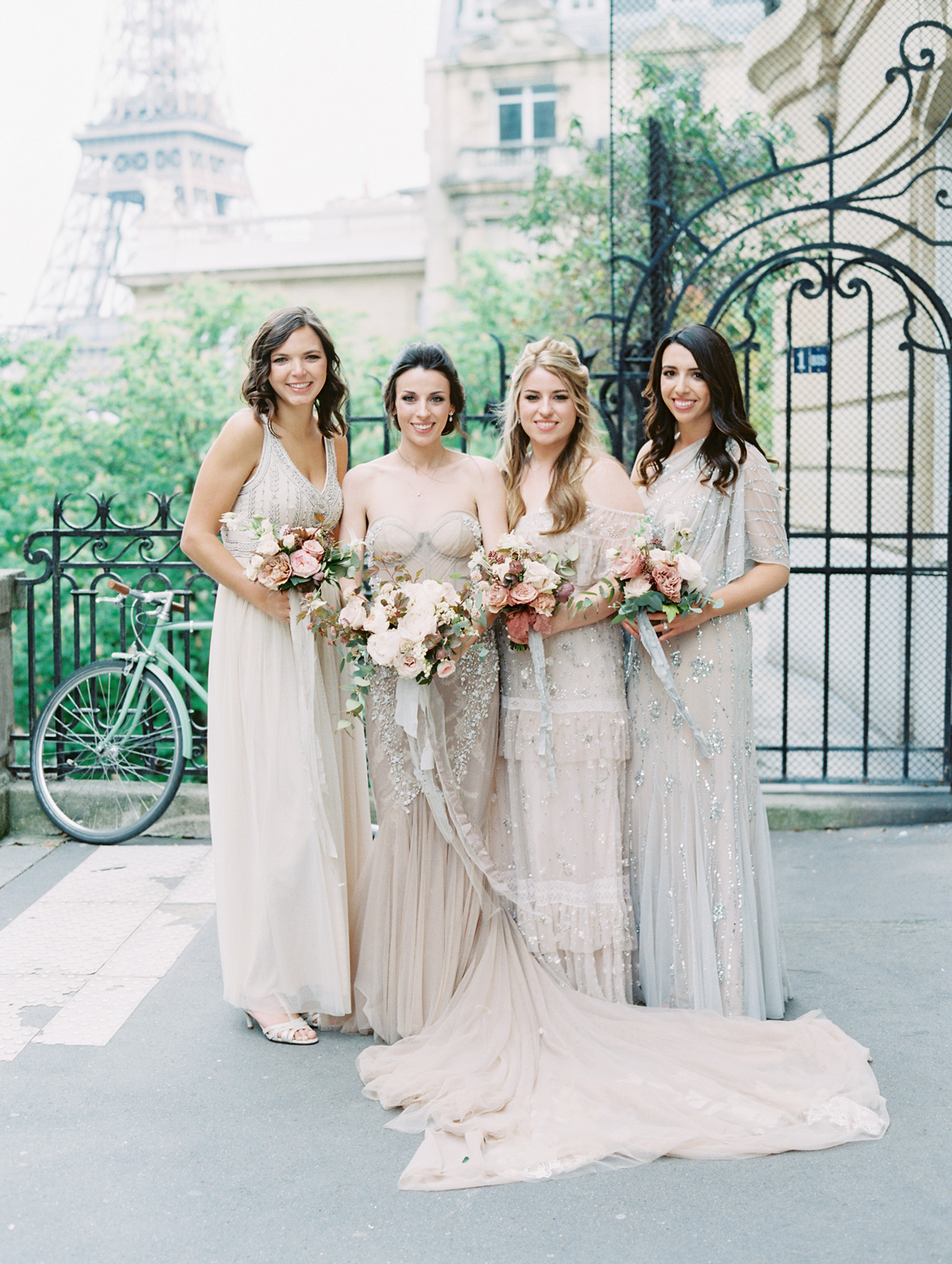 bride with bridesmaids in mismatched soft hue gowns