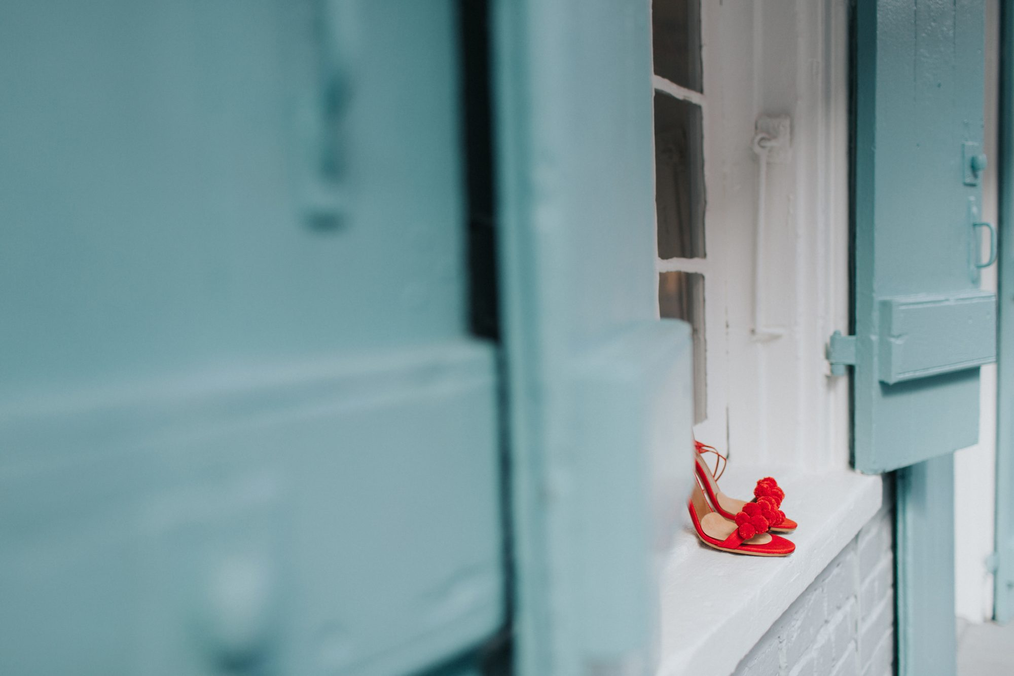 red pom pom sandals on windowsill