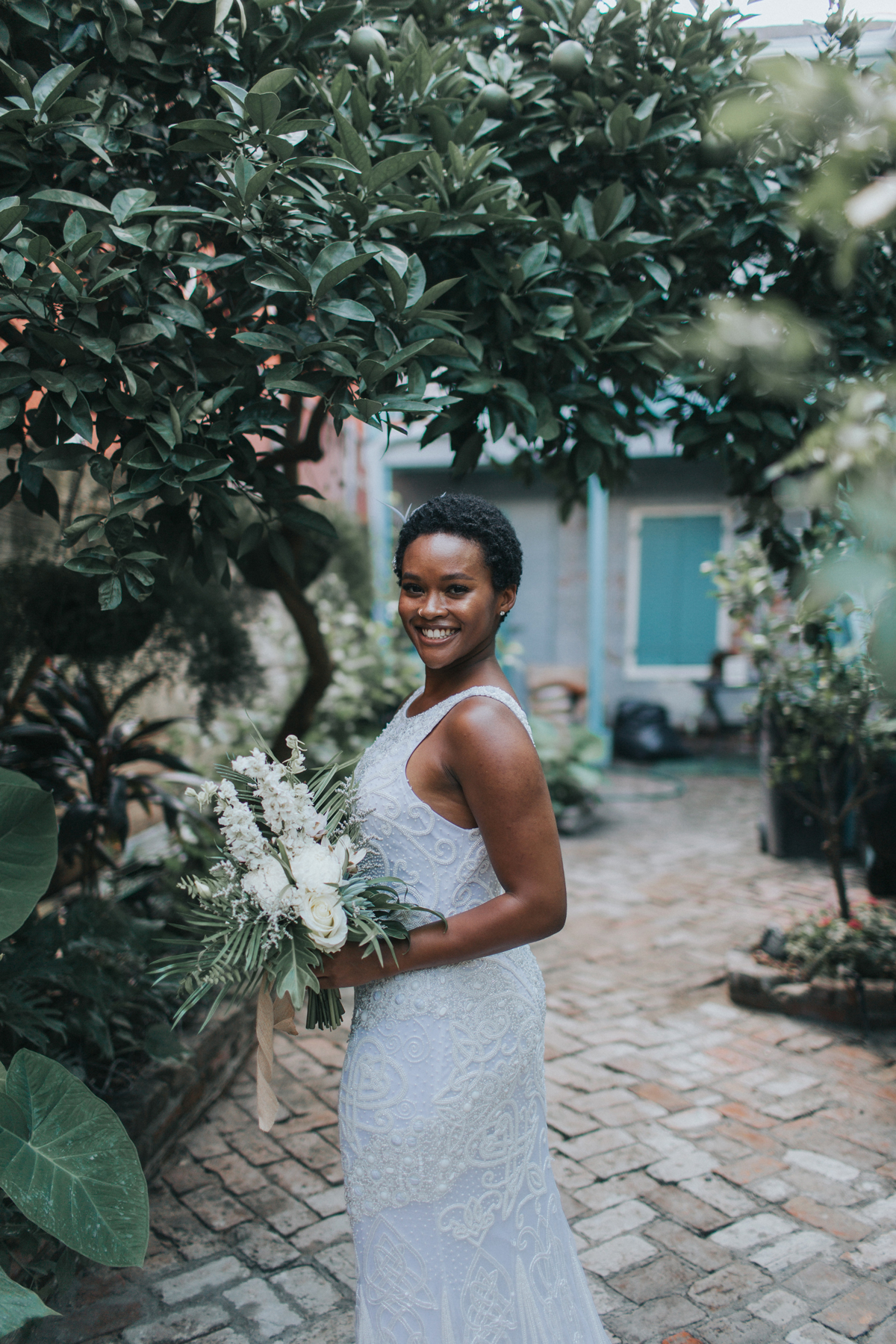 bride wearing beaded gown posing amongst greenery