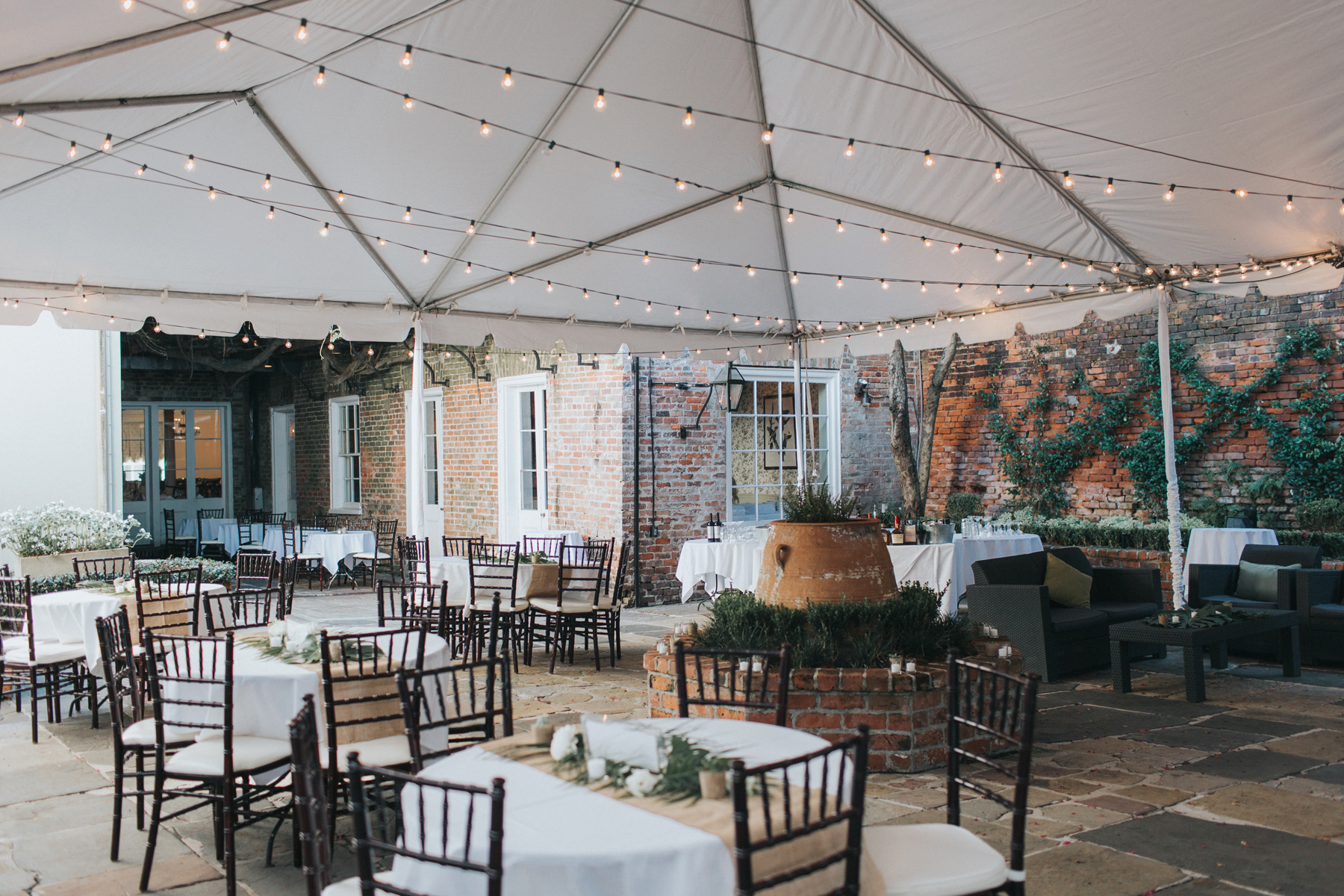 wedding reception setup beneath white tent with string lights