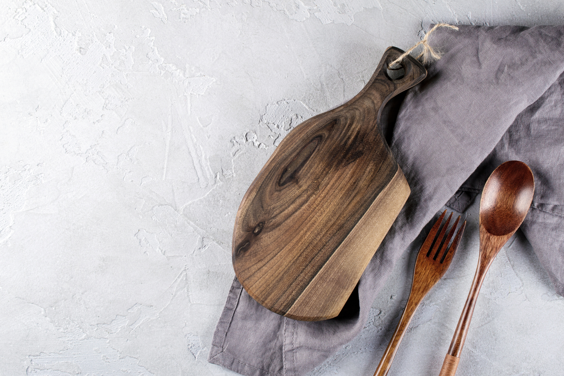 wooden cutting board on gray towel