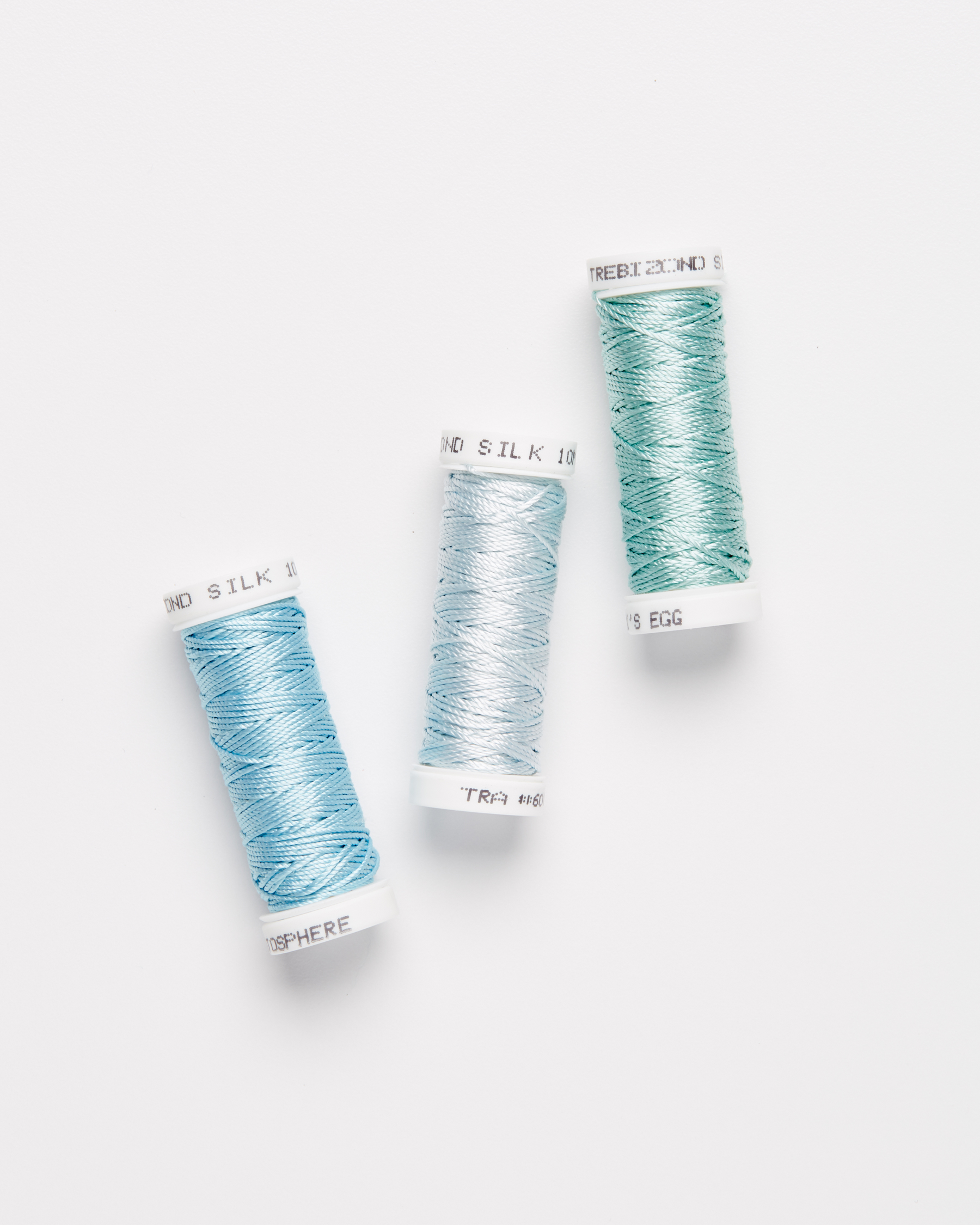 three spools of embroidery silk thread against a white background