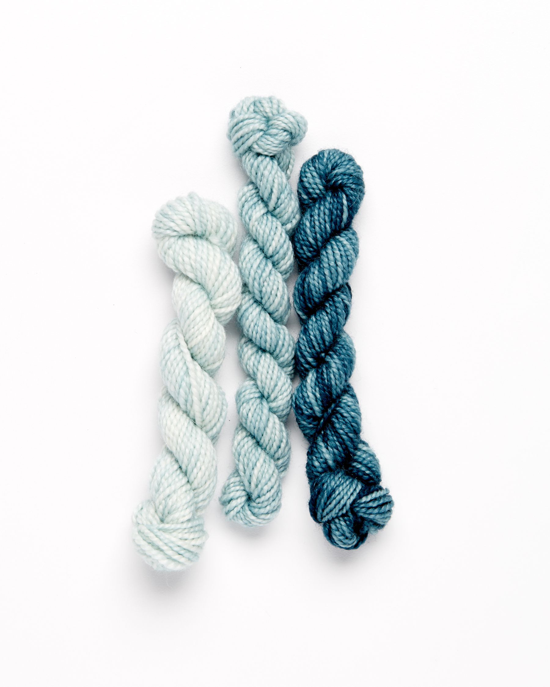 blue embroidery wool yarn against a white background