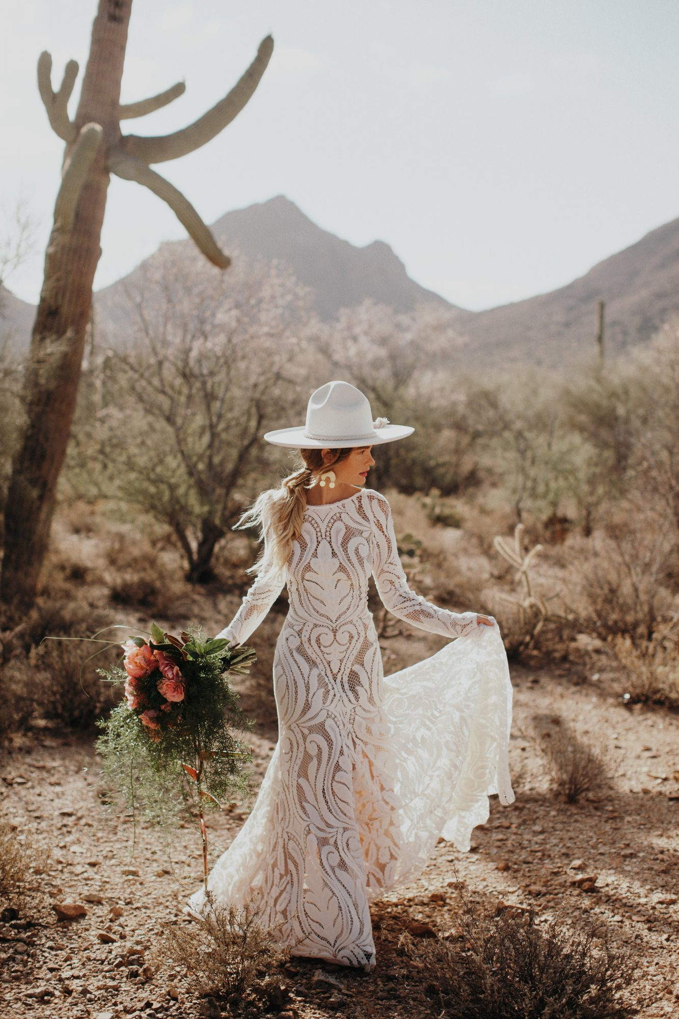 bride wearing white hat in the desert
