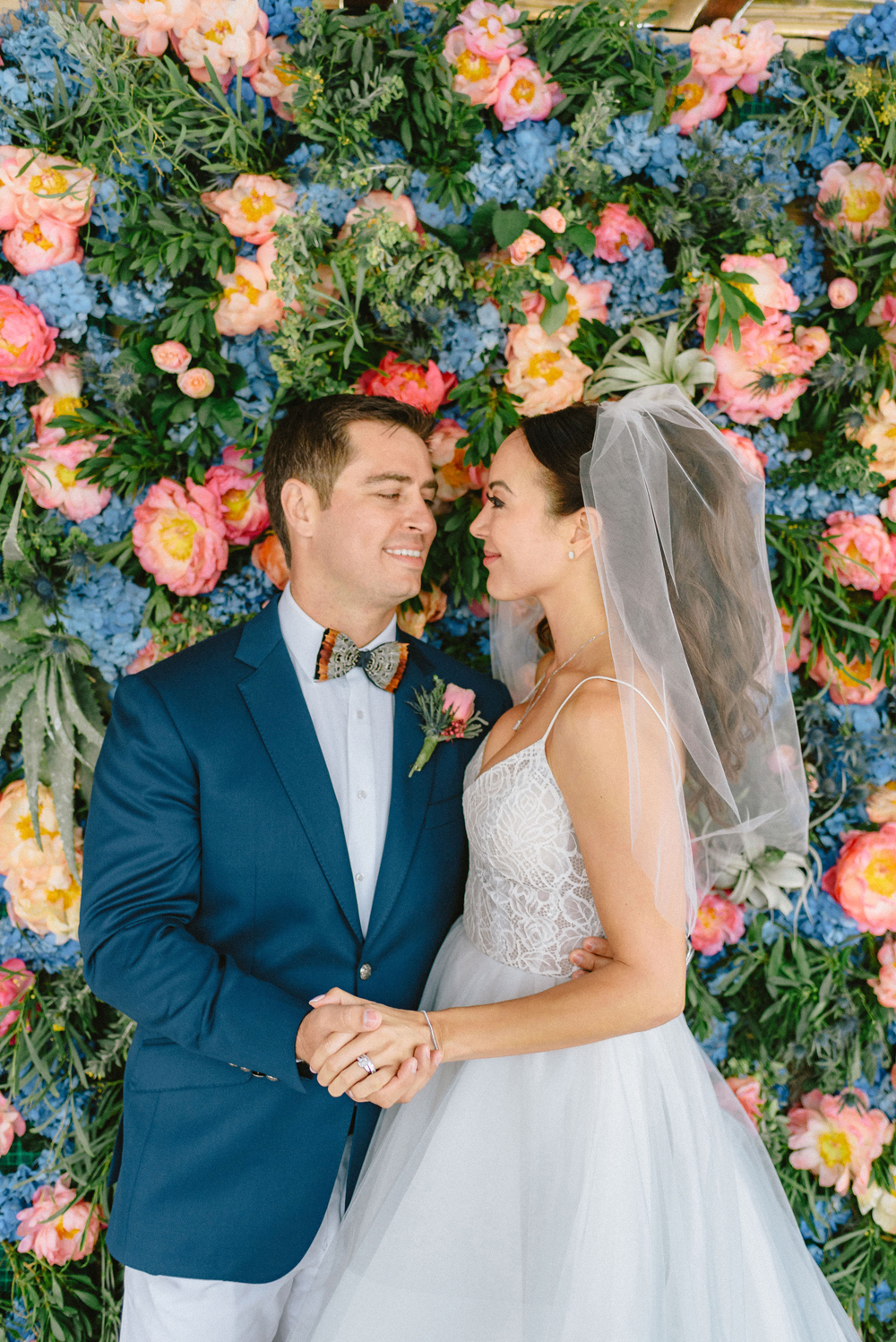 bride and groom standing in front of wedding plant wall of multi-colored flowers