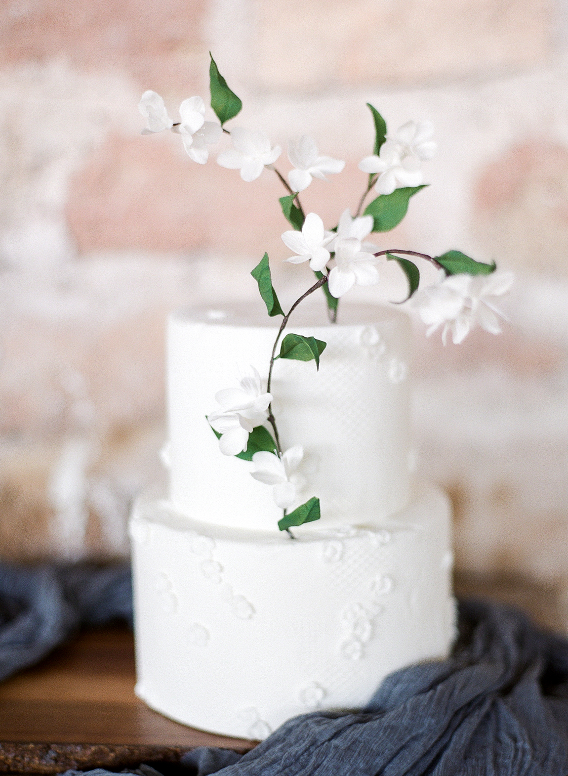two tiered white frosted cake with fondant floral accents
