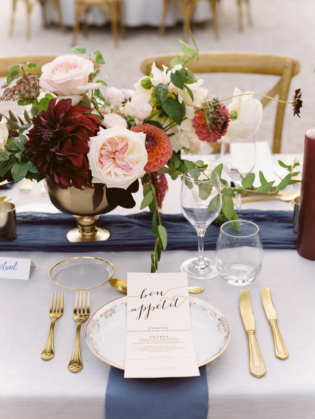 white and gold place settings with navy blue linen accents and floral centerpieces