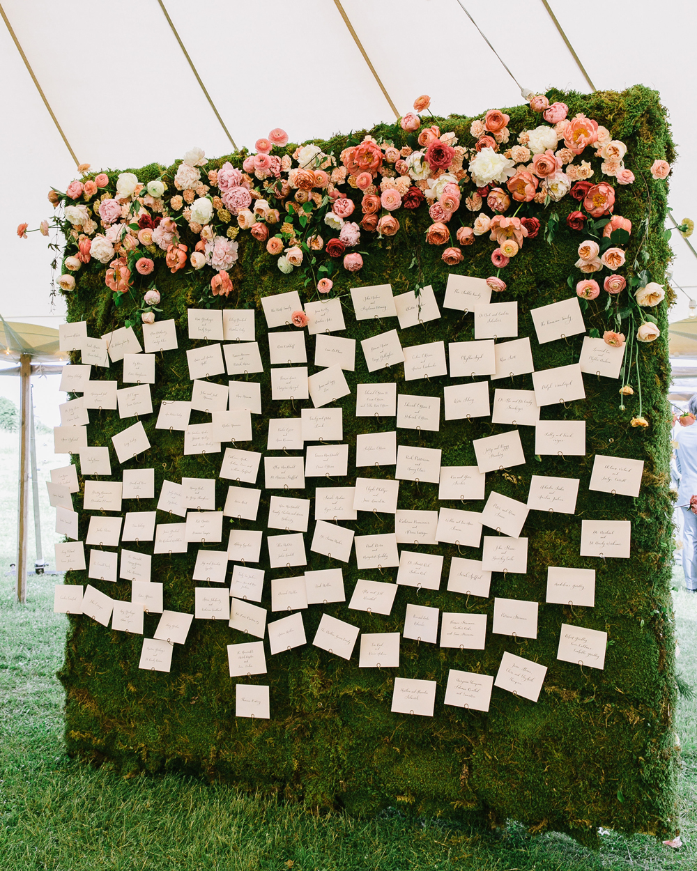 white escort cards attached to greenery wall accented with pink flowers