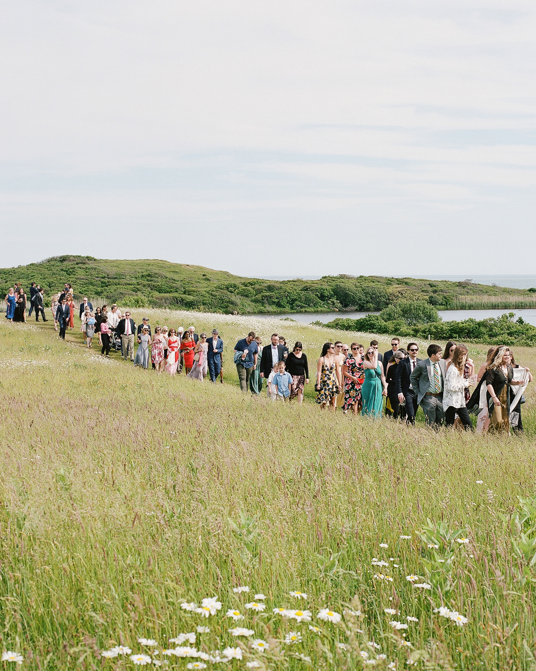 guests walking to ceremony site through pasture area