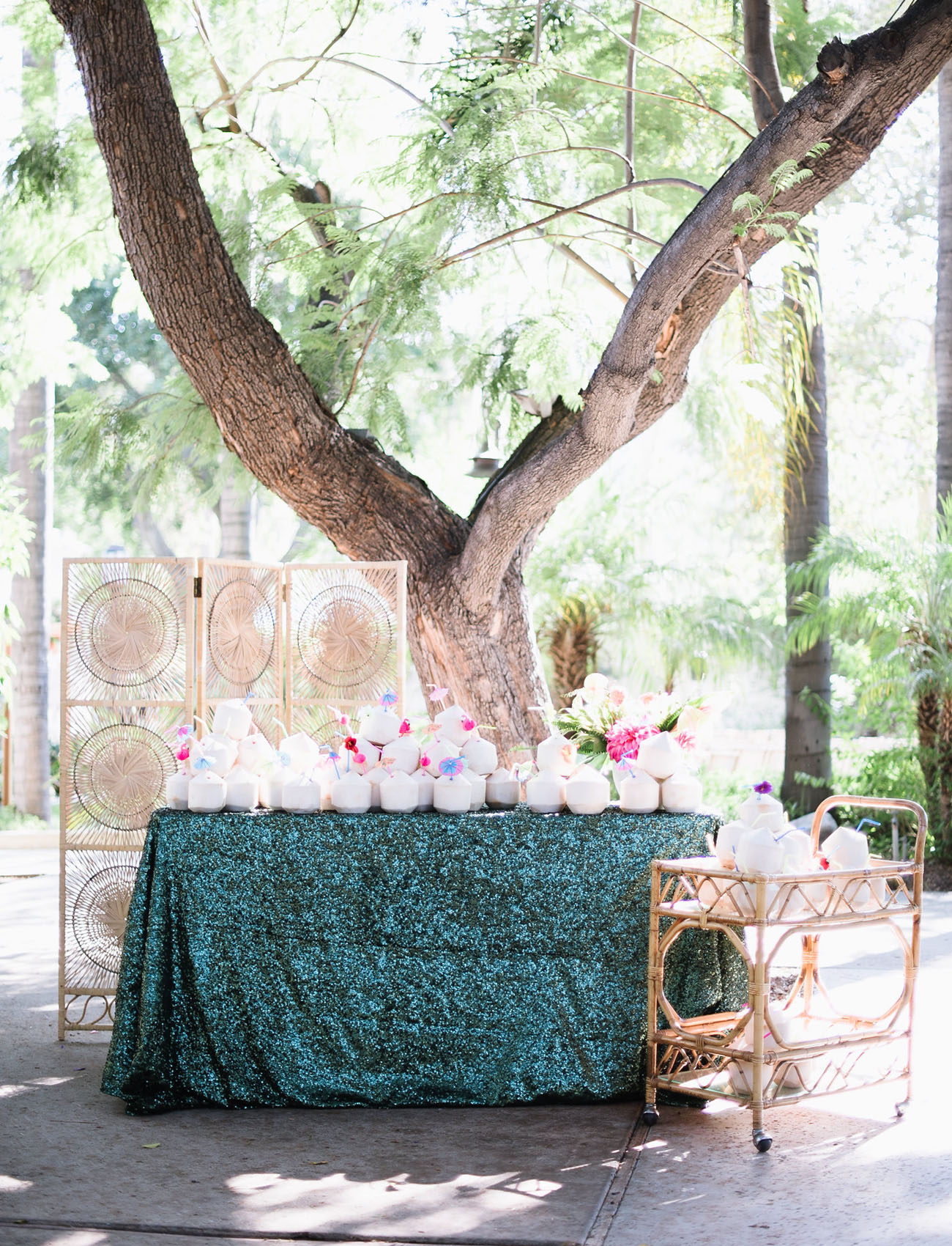 shaved coconuts with cocktail umbrellas on sequin covered table