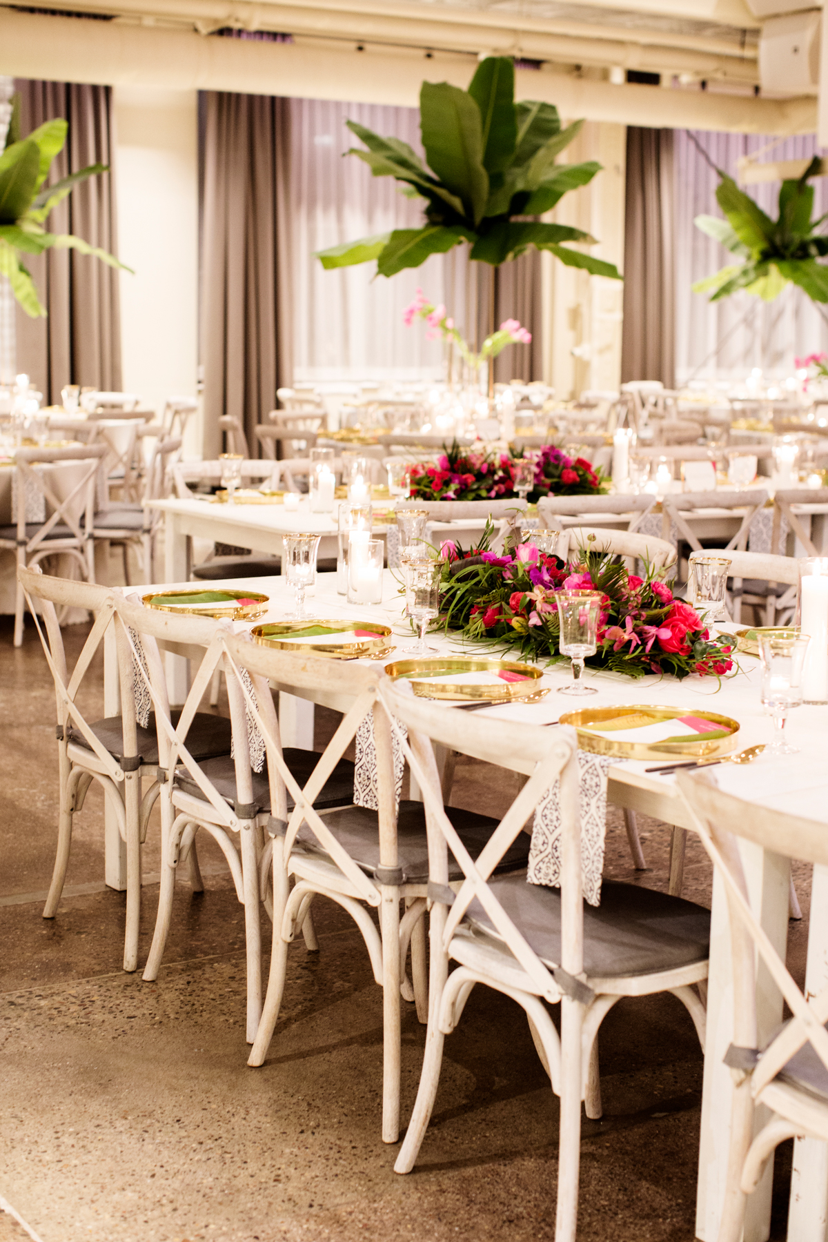 white chair and table reception set up with pink floral centerpieces