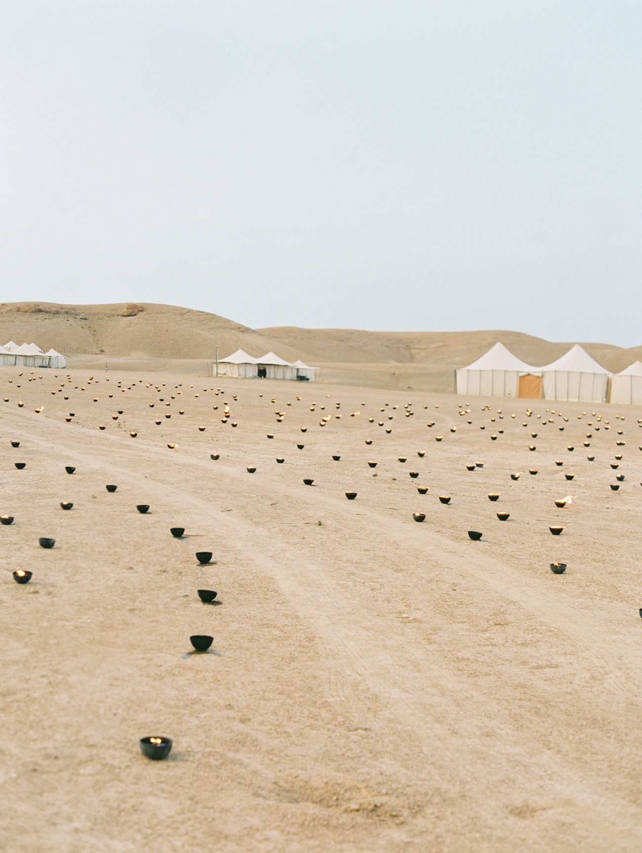desert wedding campground area with moroccan lanterns and white tents