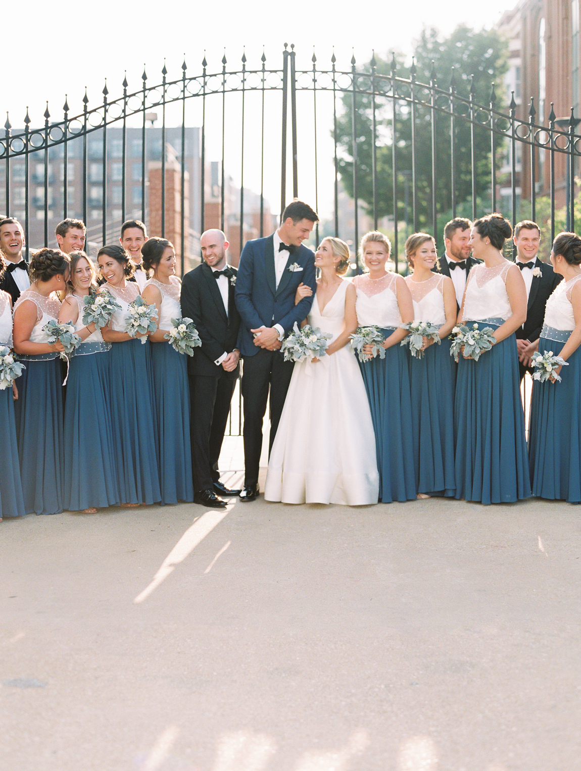 bride and groom with wedding party wearing black tuxedos and dark blue skirts with white tops